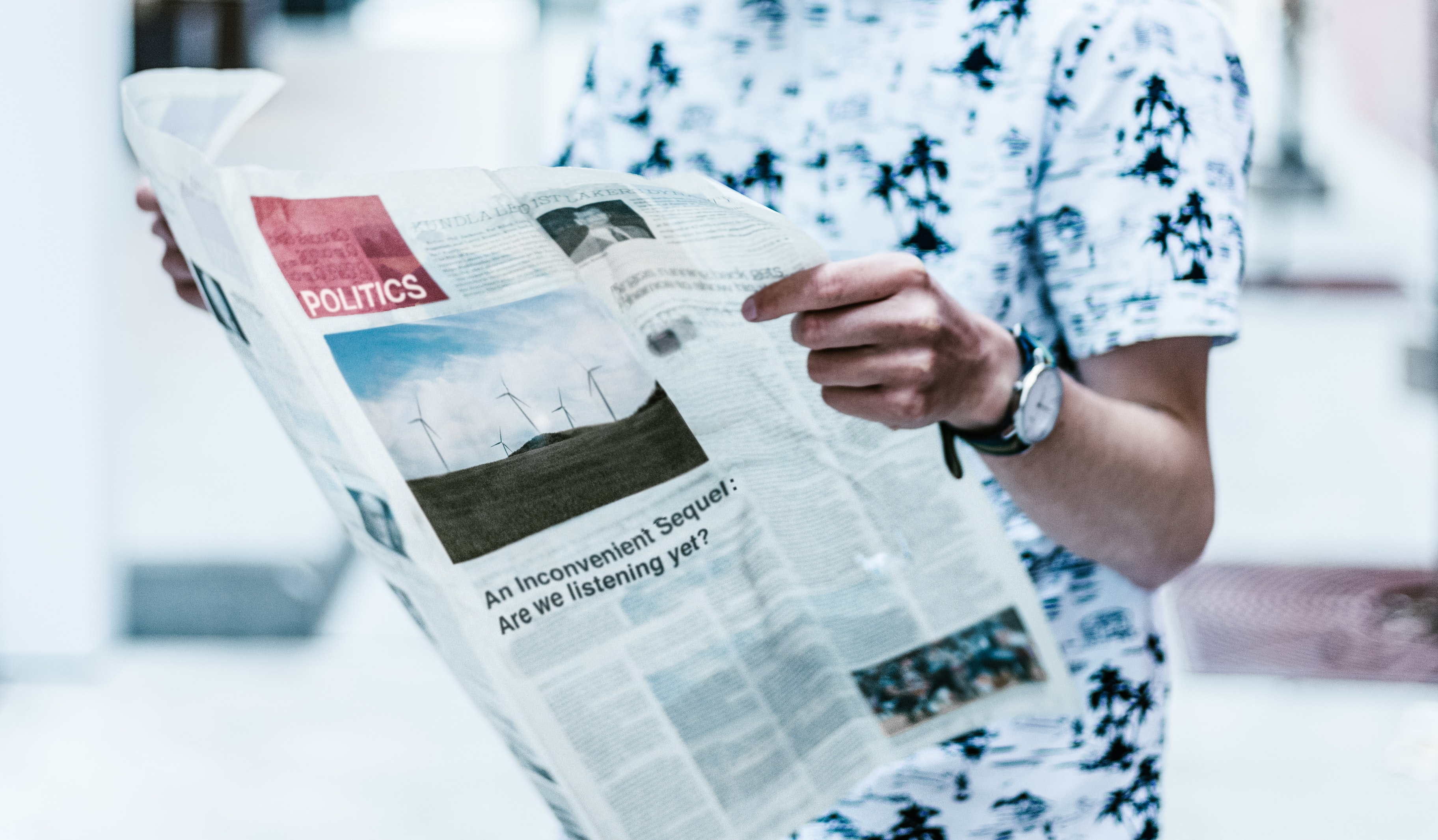A standing man in a black and white shirt reading a newspaper