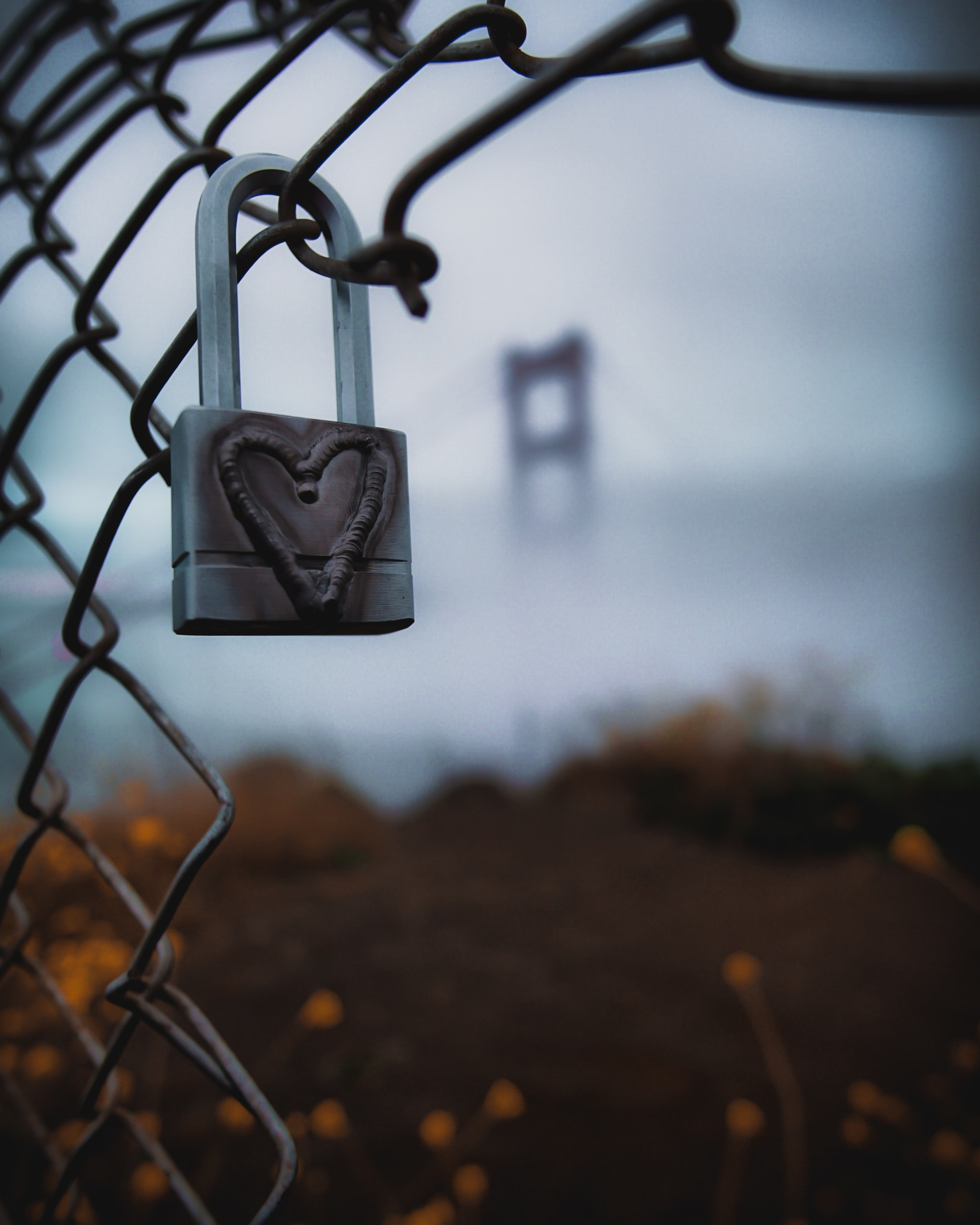 A lock on a fence with a heart etched in.
