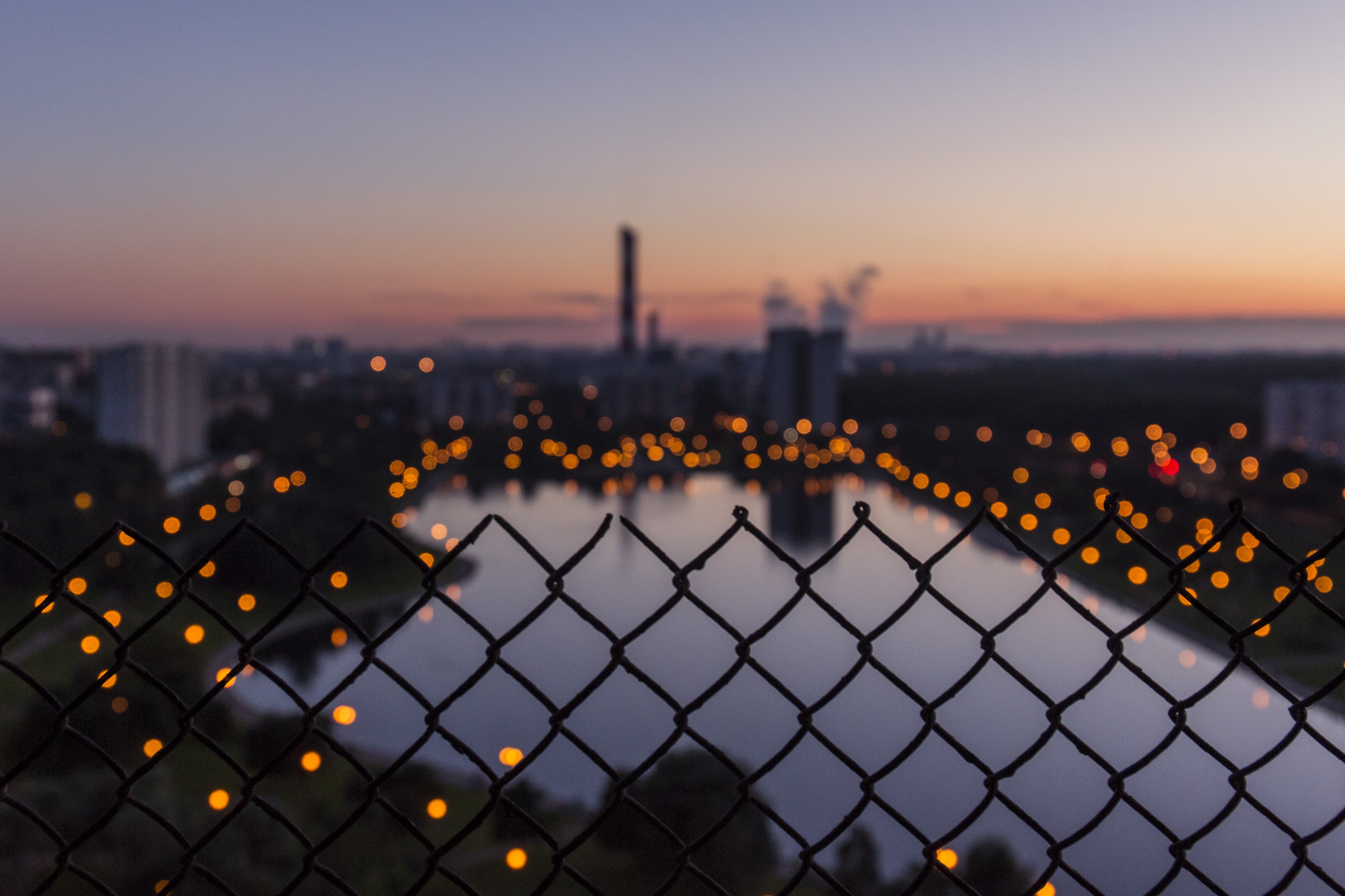 Looking across the city of Moscow through the silhouette of a fence.