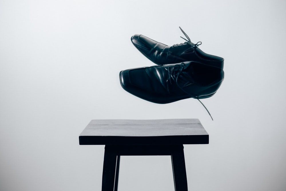 Two black leather shoes suspended over a black stool