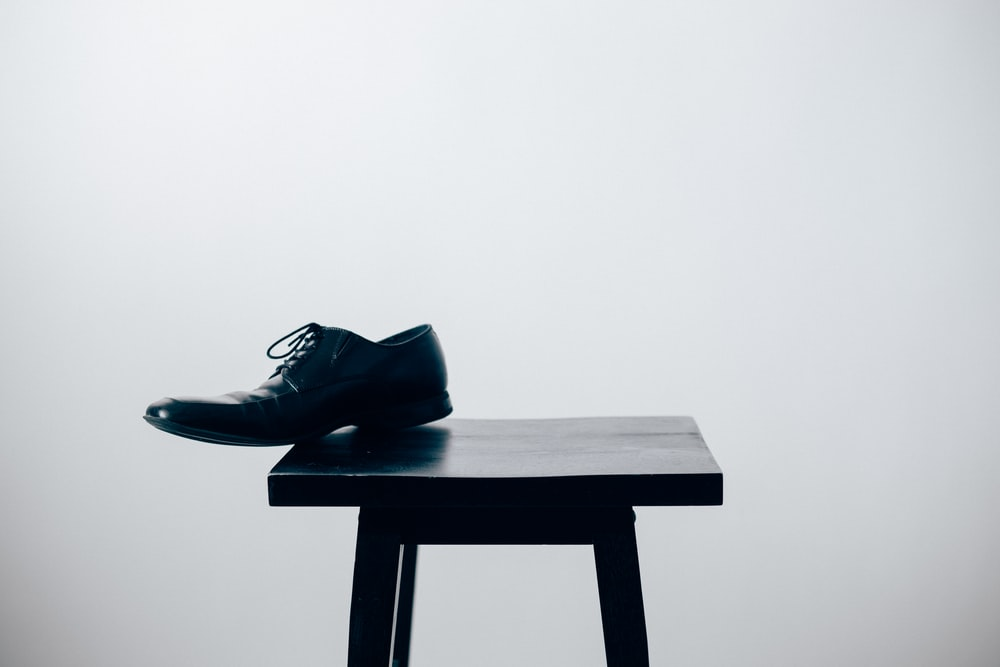 black leather dress shoe on black wooden table