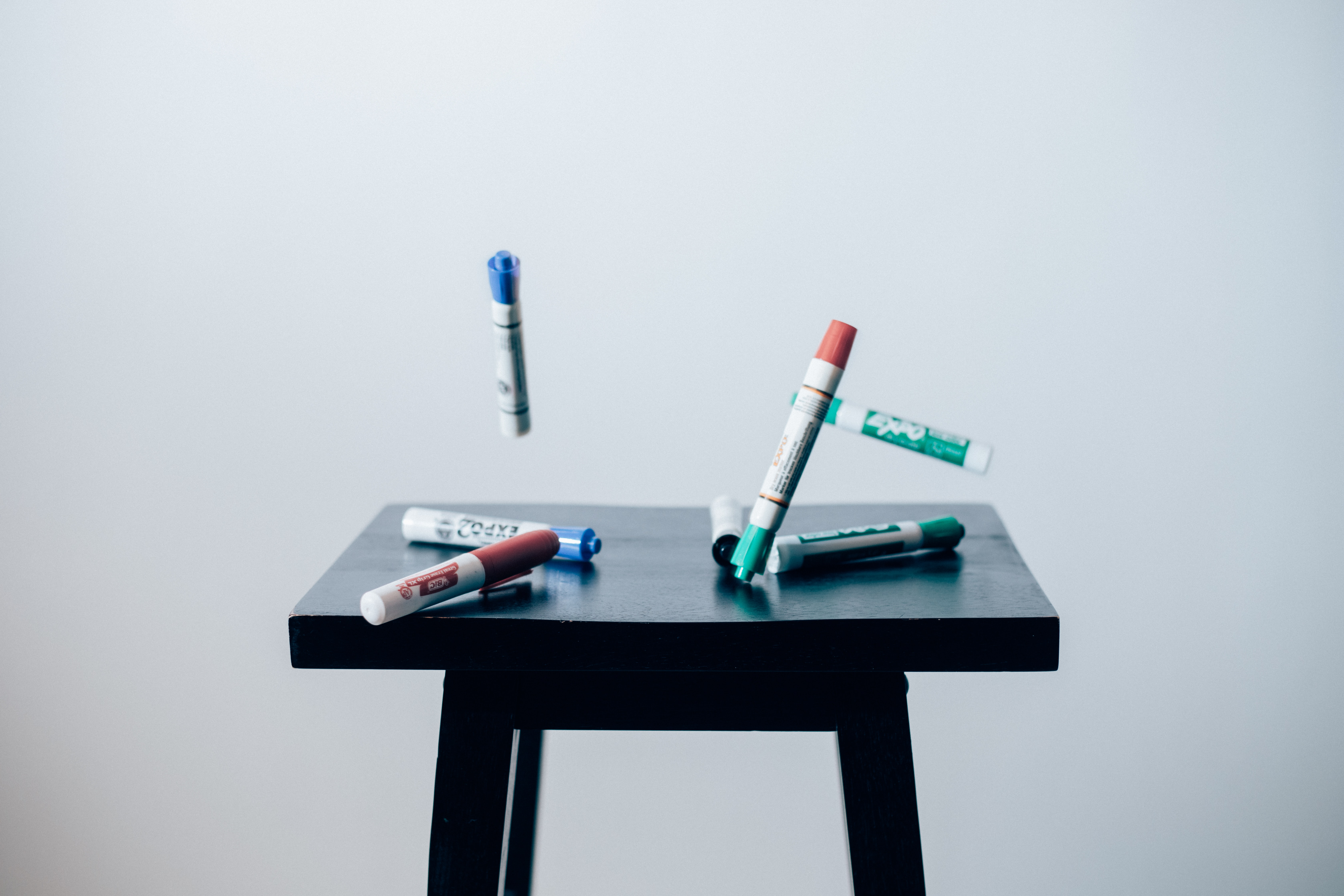 Marker pens are being dropped on a black stool.