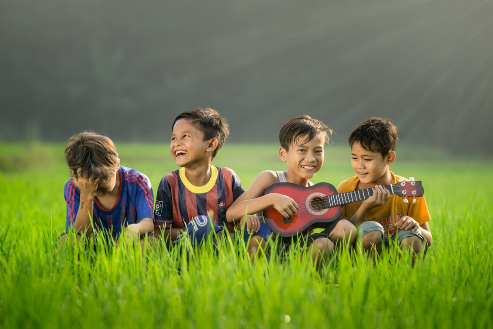 four boys laughing and sitting on grass during daytime