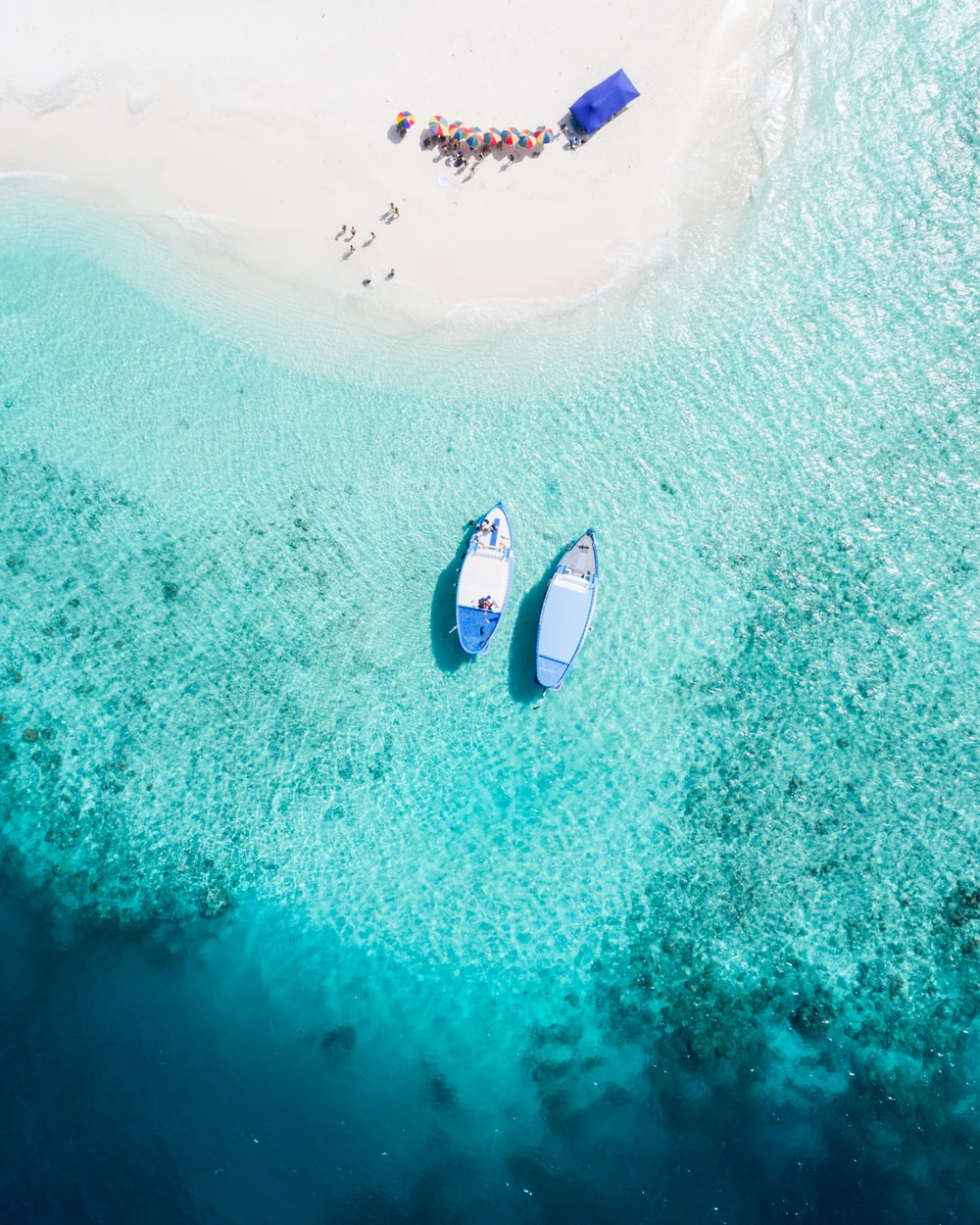 aerial view of two blue boats