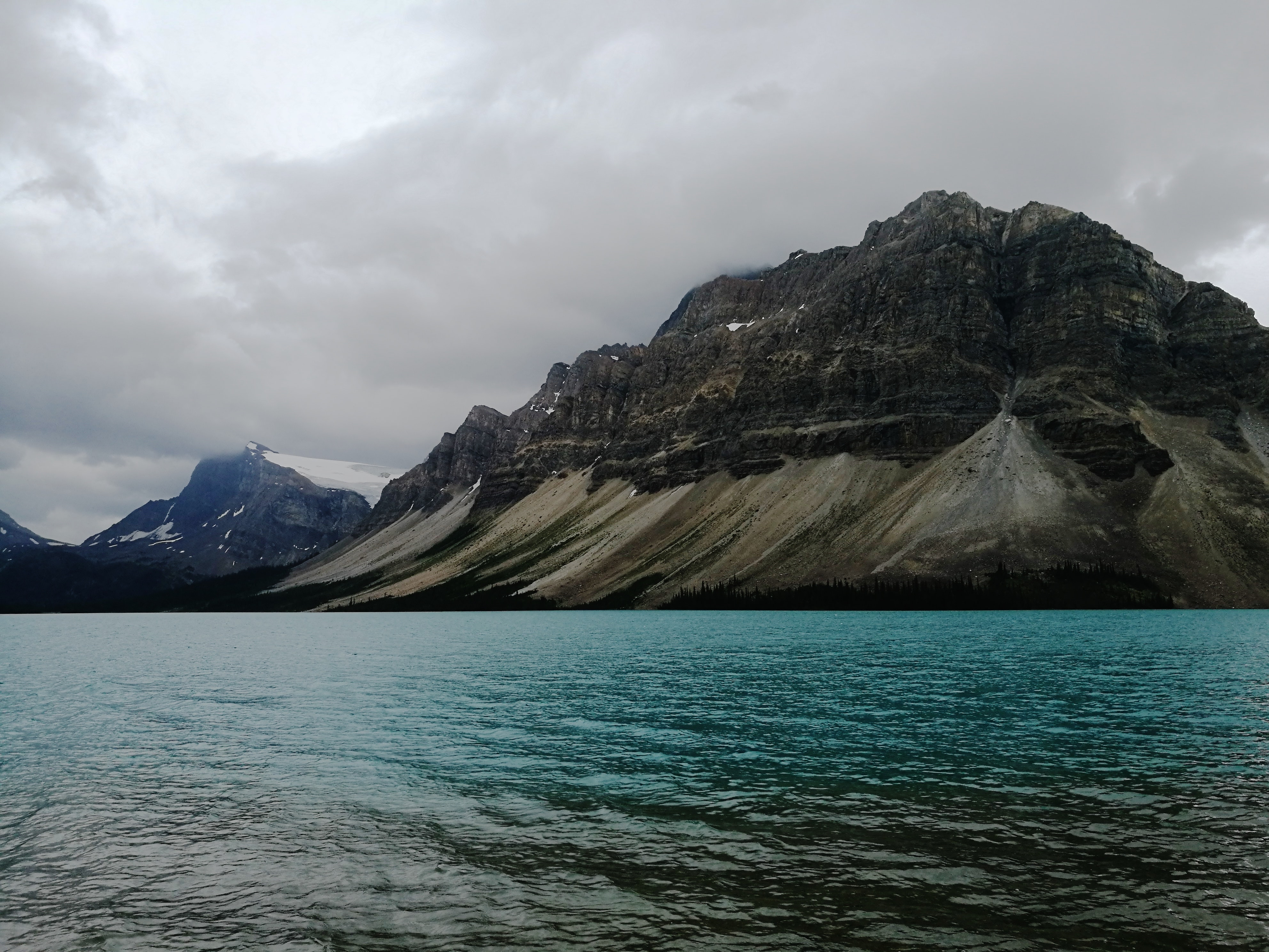 black and brown rocky mountain beside body of water under cloudy sky