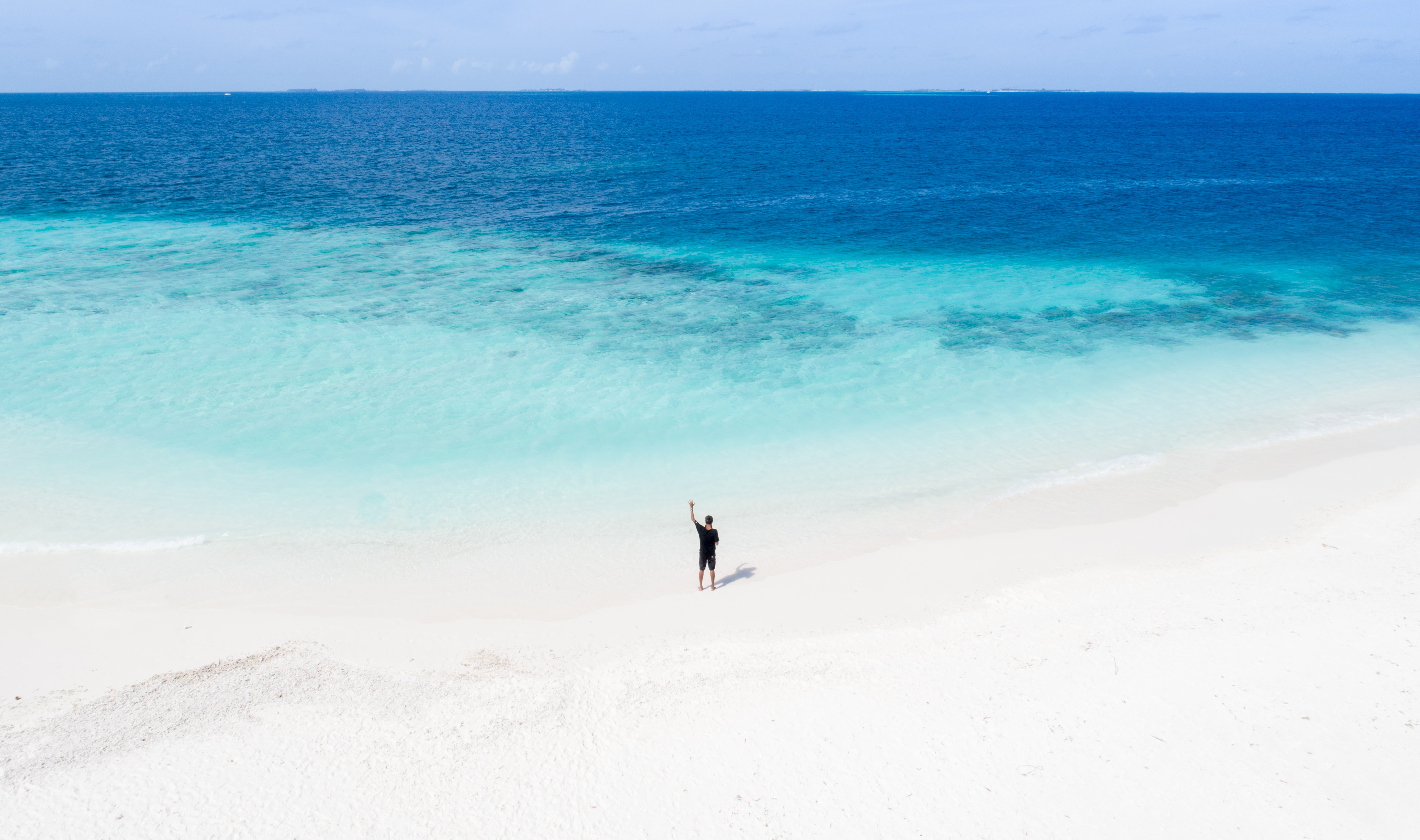 person standing on white sand beach