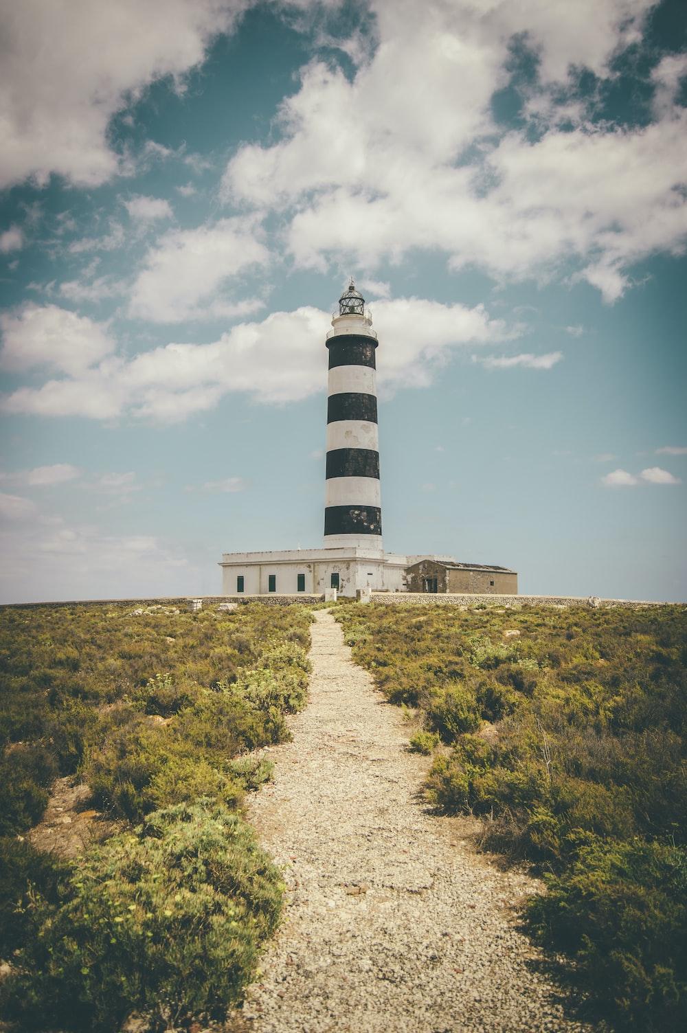 lighthouse under cumulus clouds and blue calm sky