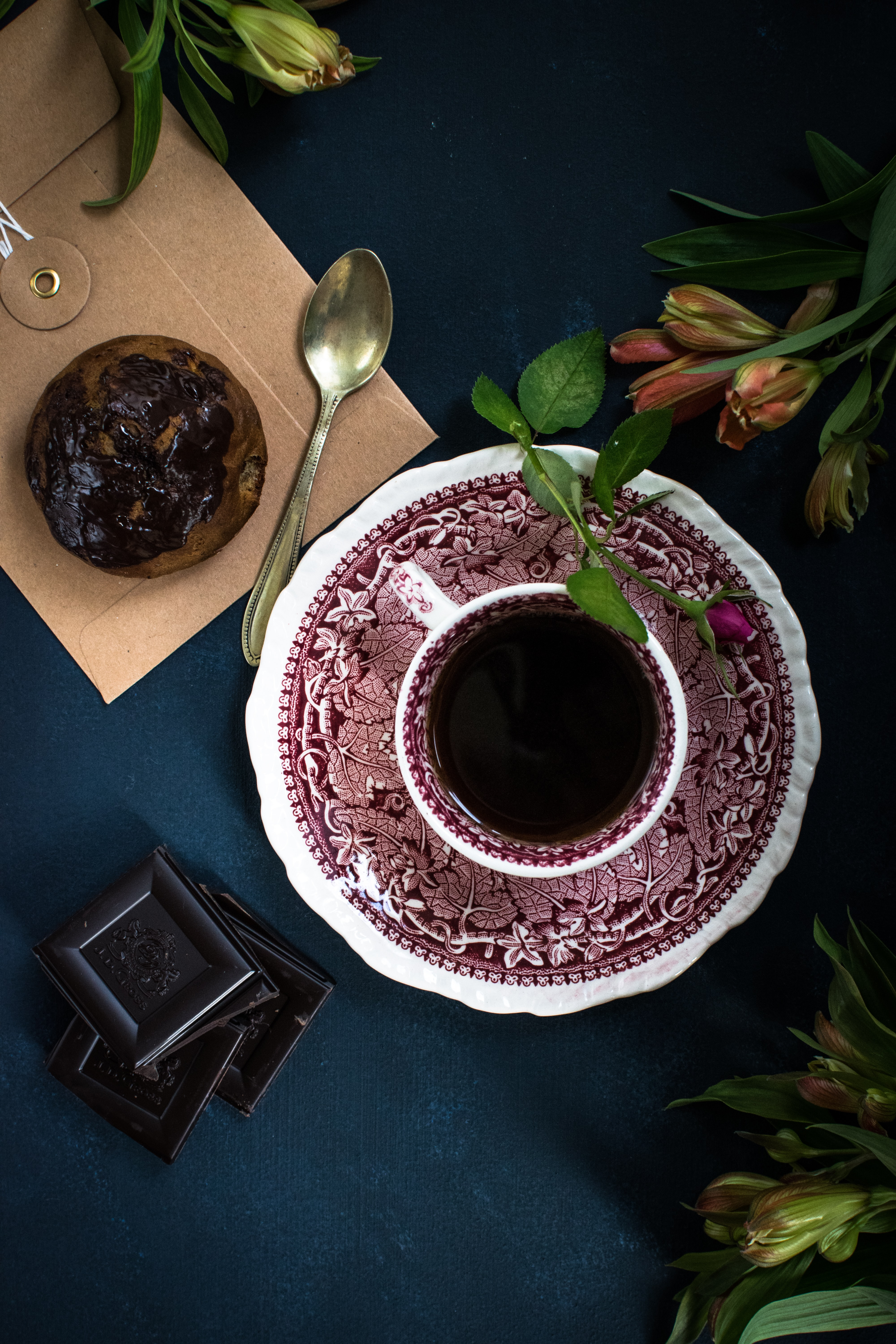 coffee served on white and red ceramic cup beside chocolate cupcake