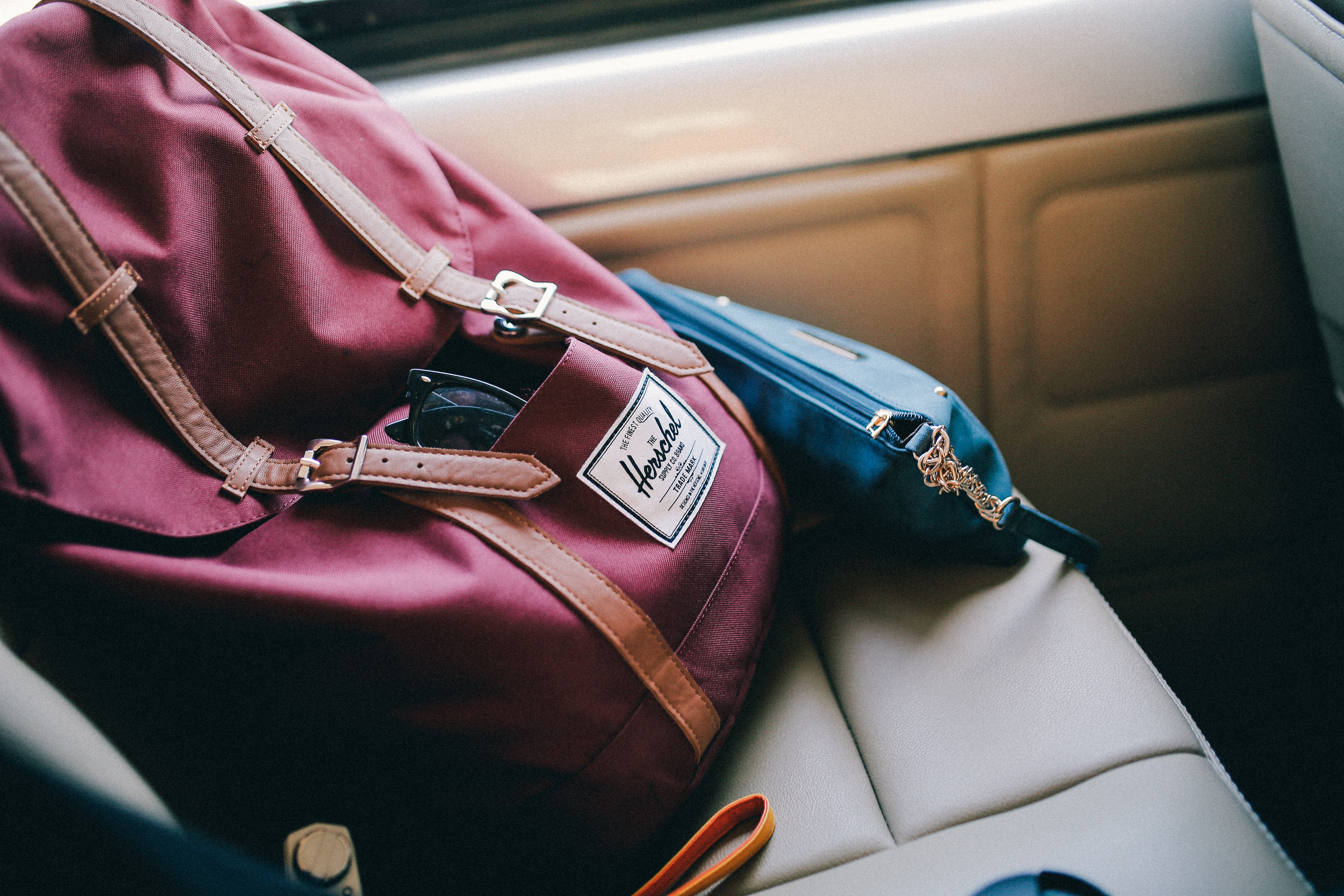 maroon Herschel bag inside car