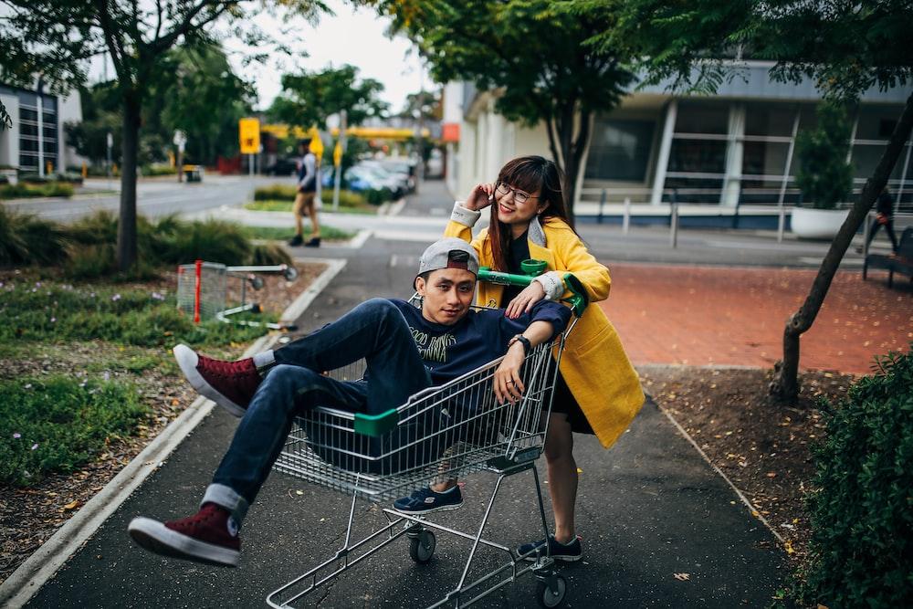 man sitting in shopping cart during daytime