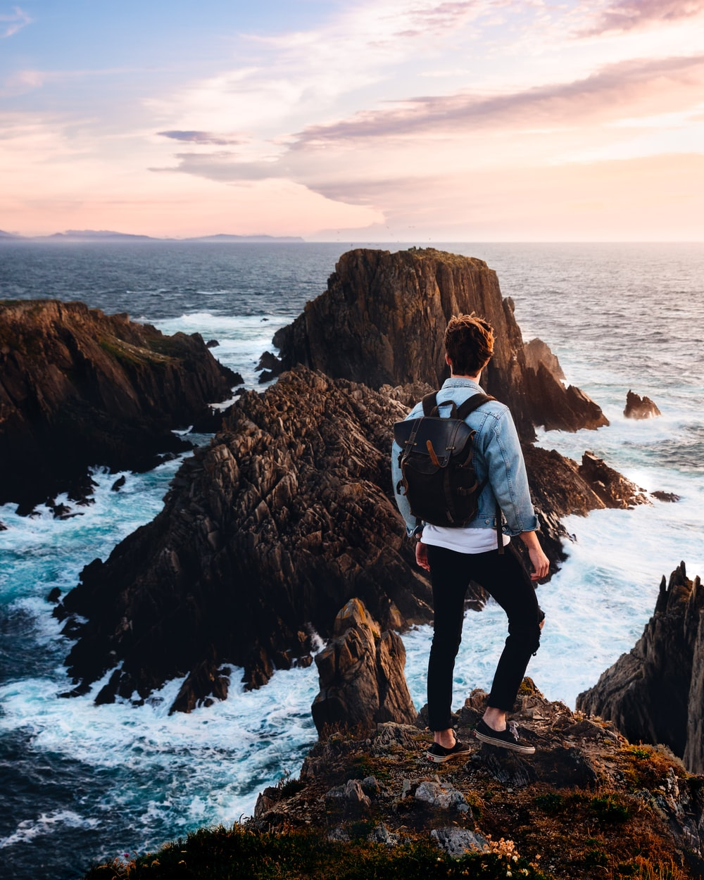 man standing near cliff looking at body of water during daytime