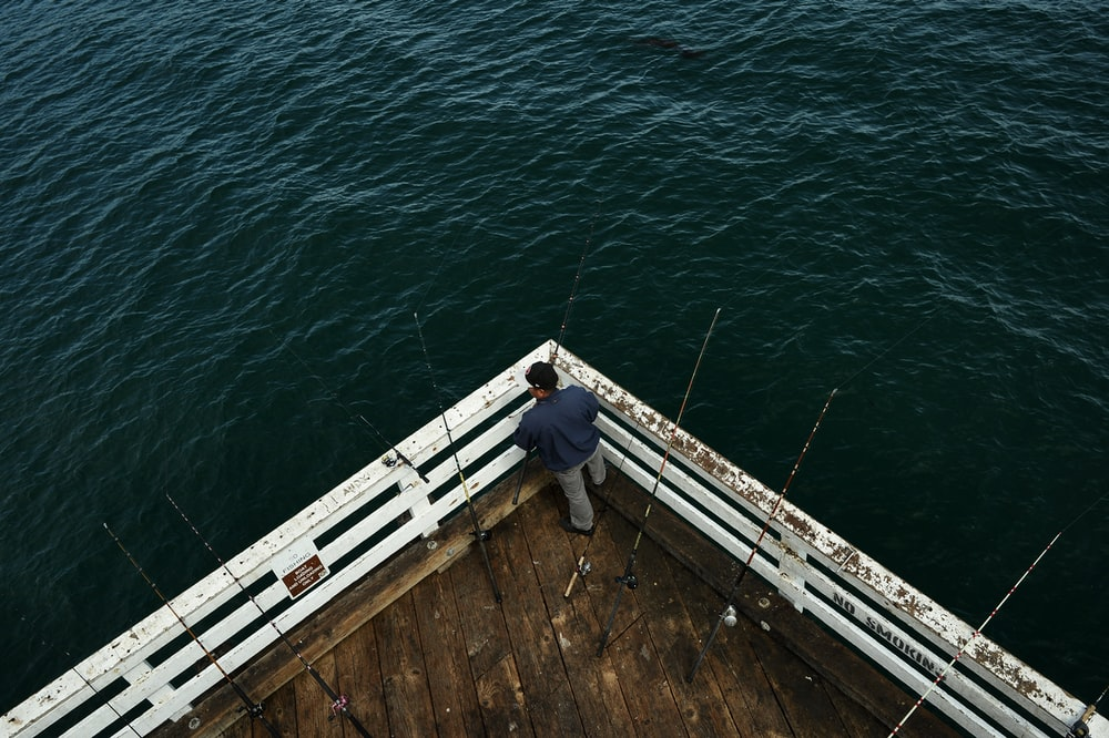 man beside dock fishing