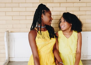 two girl's in yellow sleeveless dresses sitting on white wooden bench during daytime