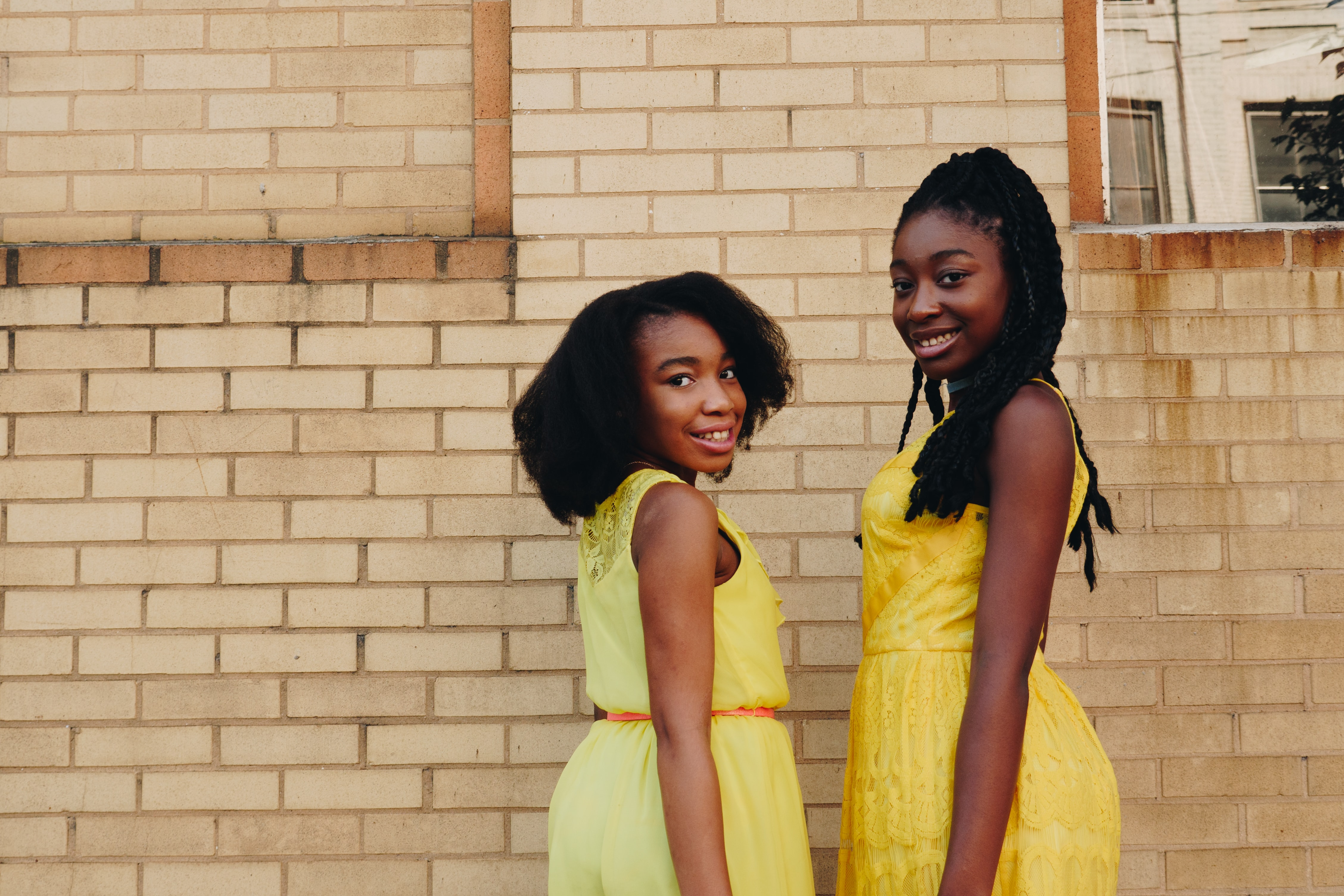 two women wearing yellow sleeveless dresses near brown brick