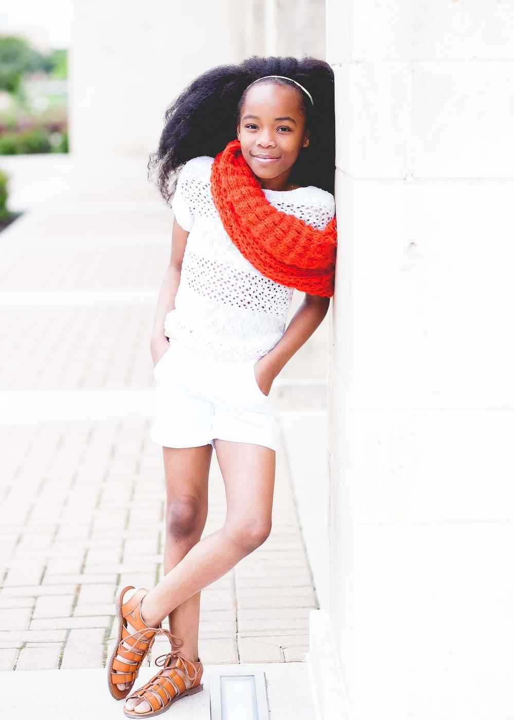 smiling girl in white shirt and shorts wearing red scarf during daytime