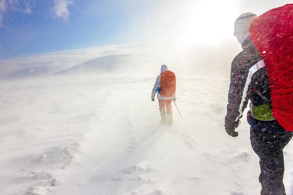 two men walking on snow under blue sky