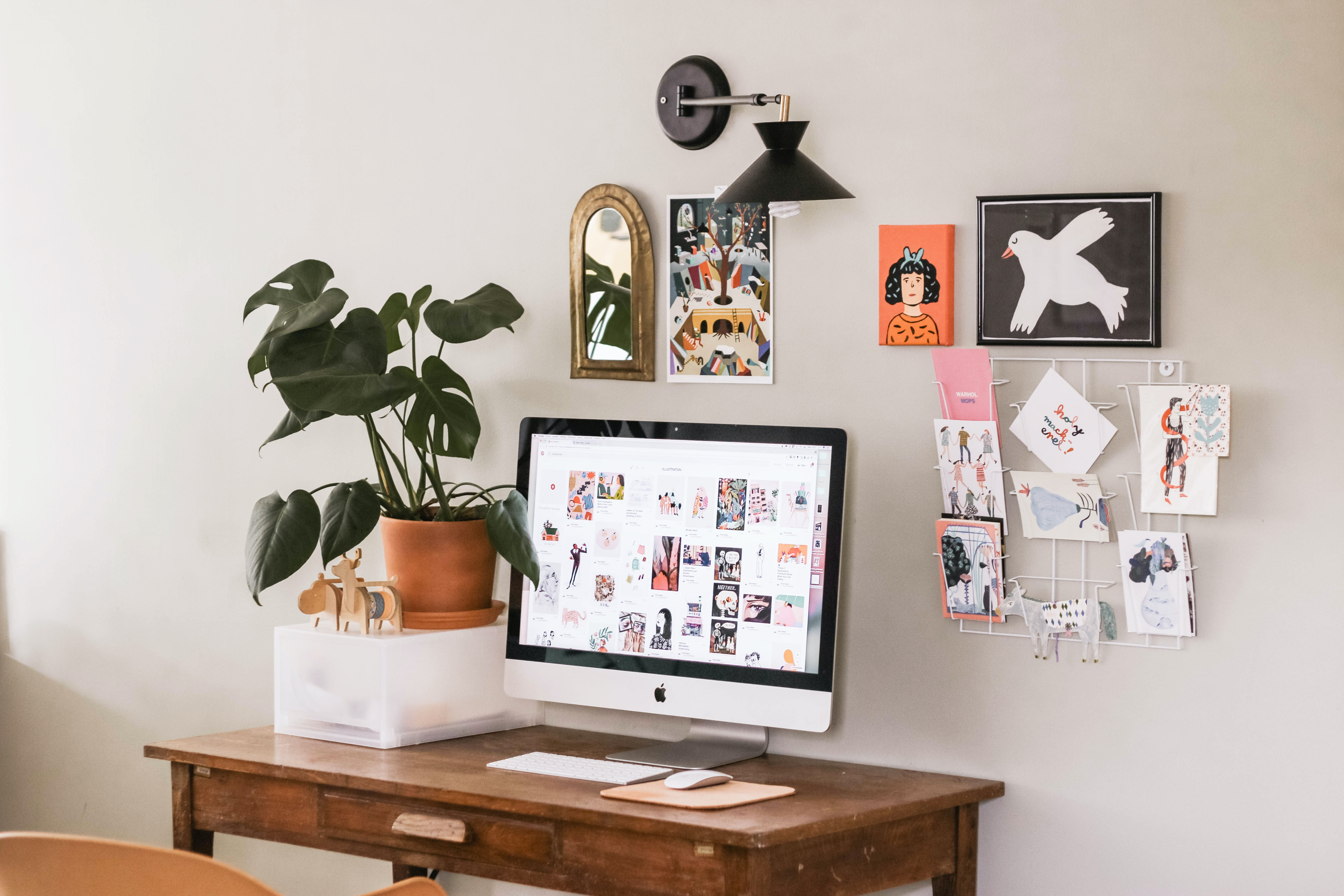 A quaint computer workspace with colorful pictures and postcards on the wall