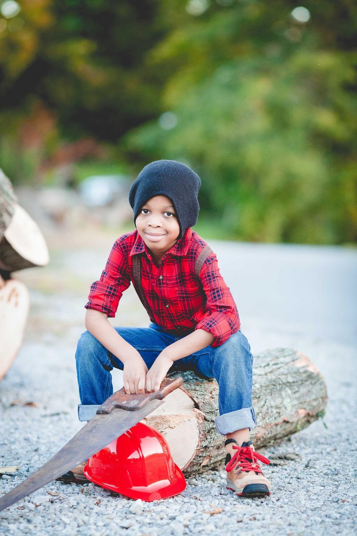 boy sitting on log holding handsaw over red hard hat