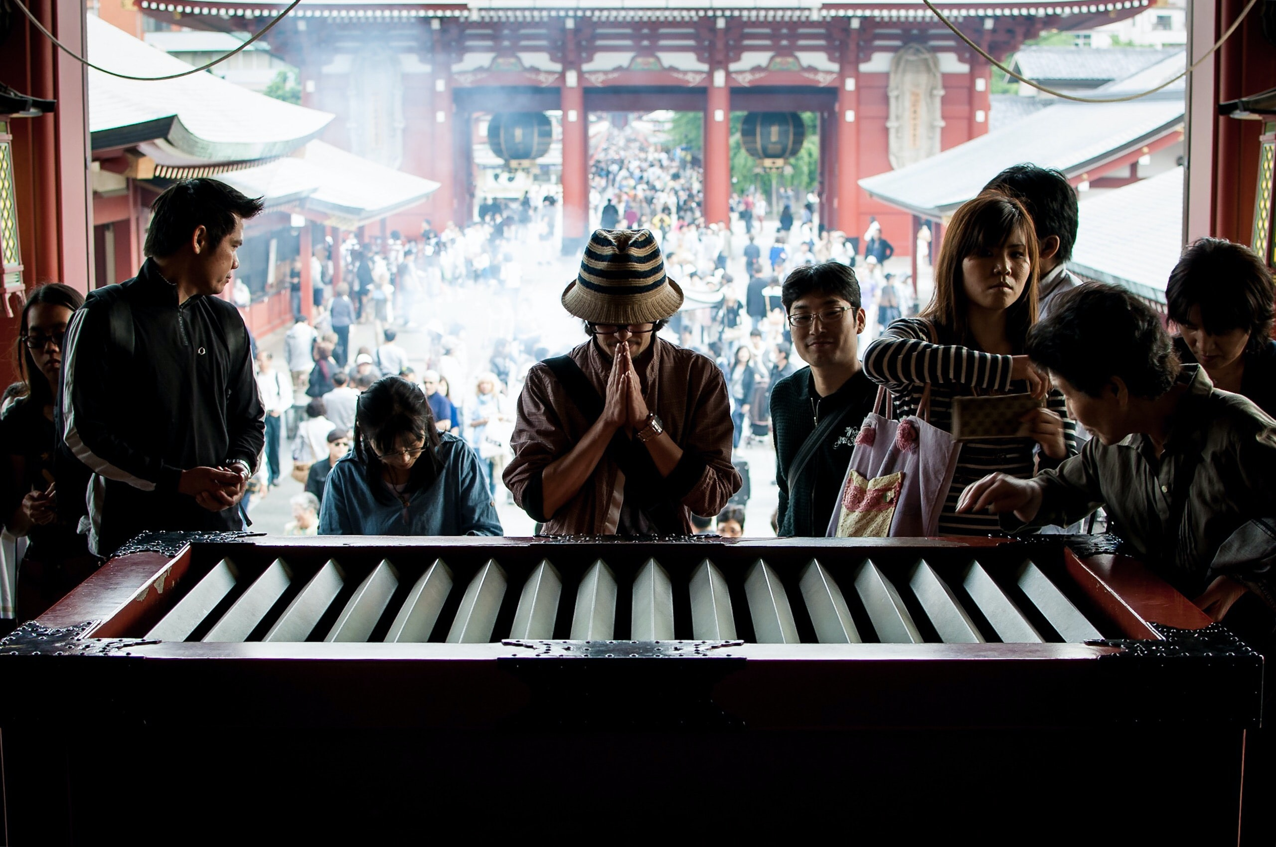 Diverse group of tourists visit and pray at a landmark Asian temple