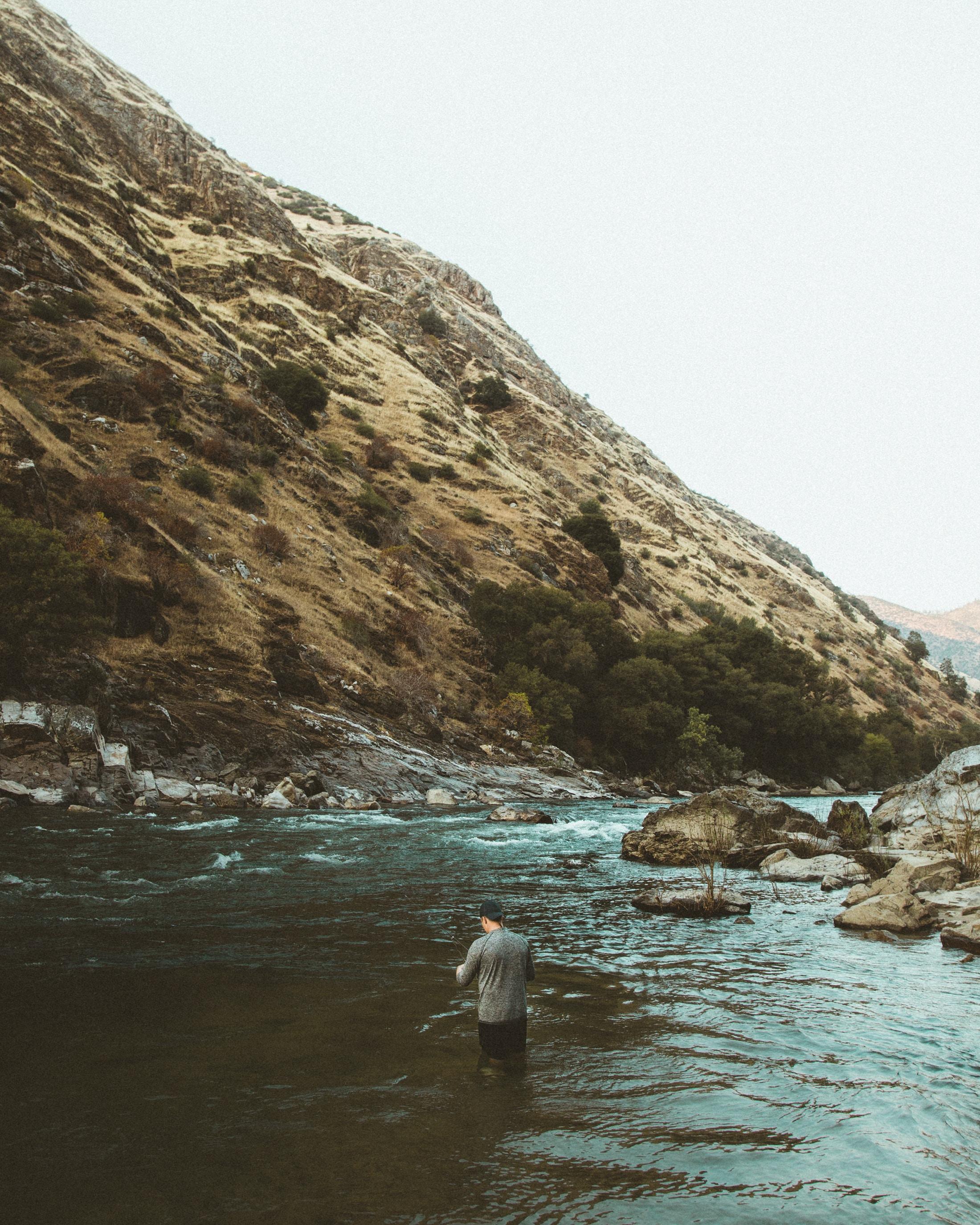 man in water near hill