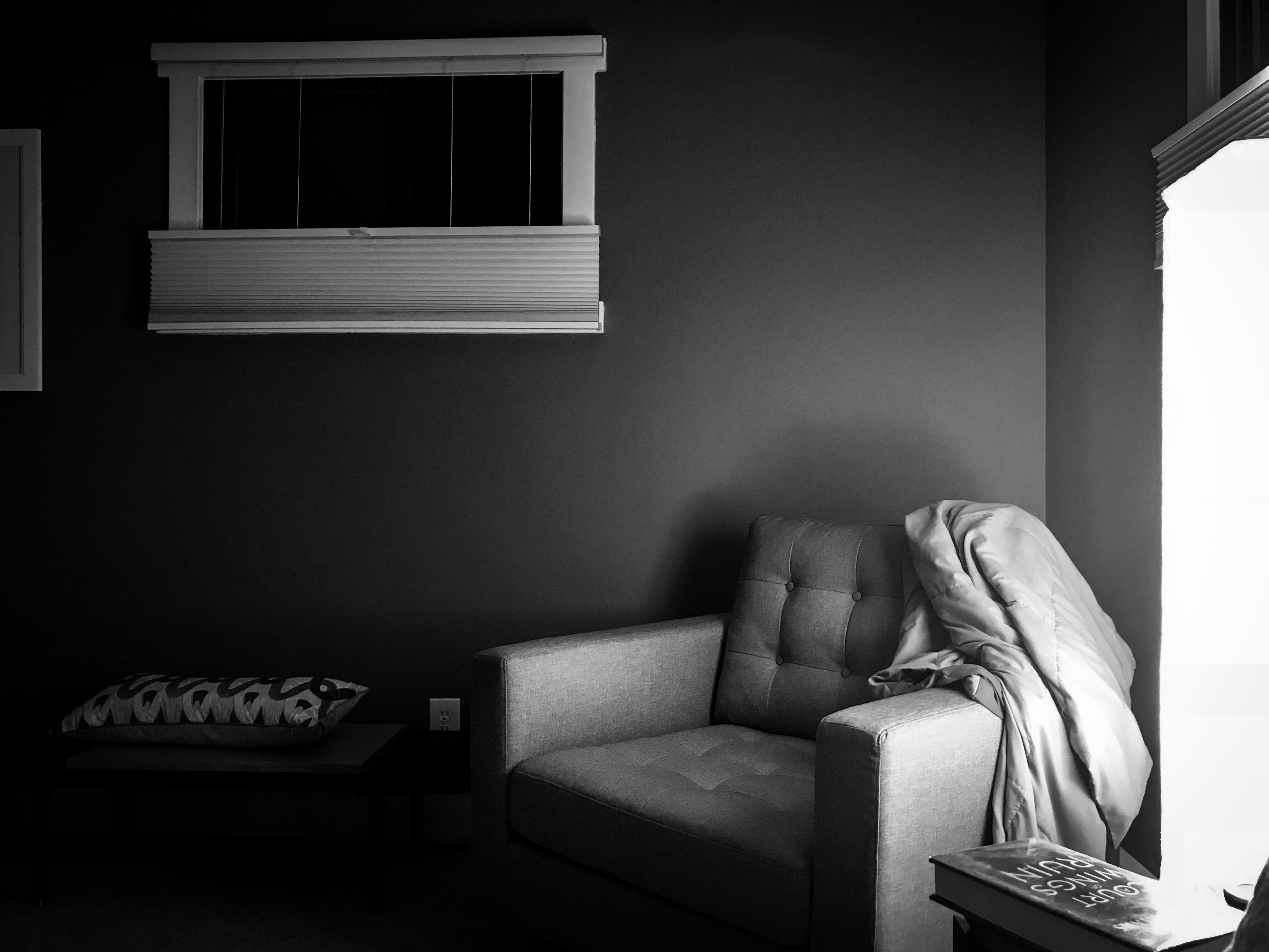 grayscale photography of sofa chair on corner