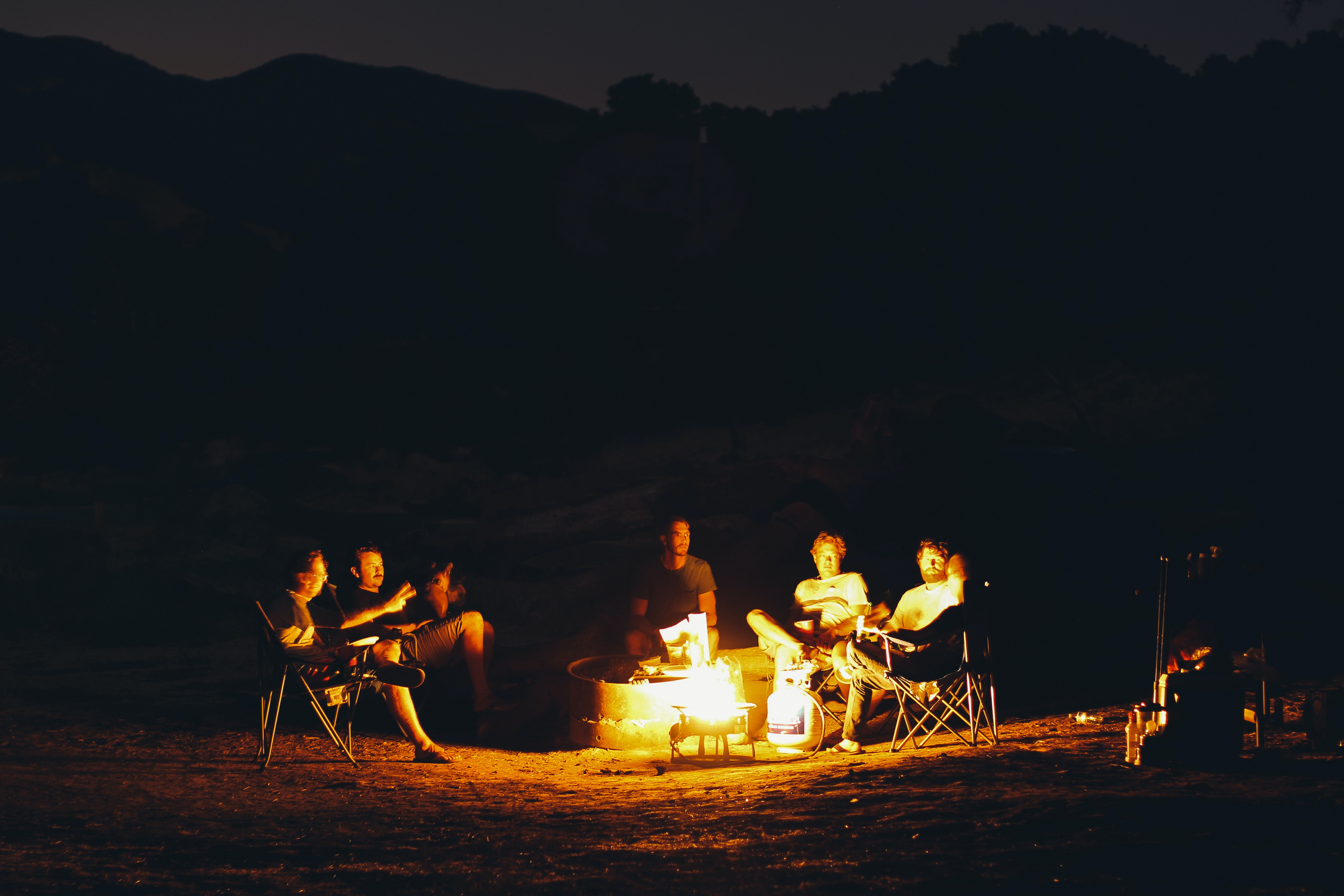 group of people seating around bonfire