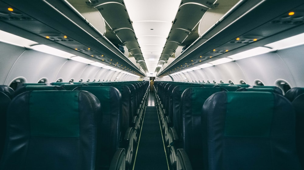 person taking photo of chairs inside plane