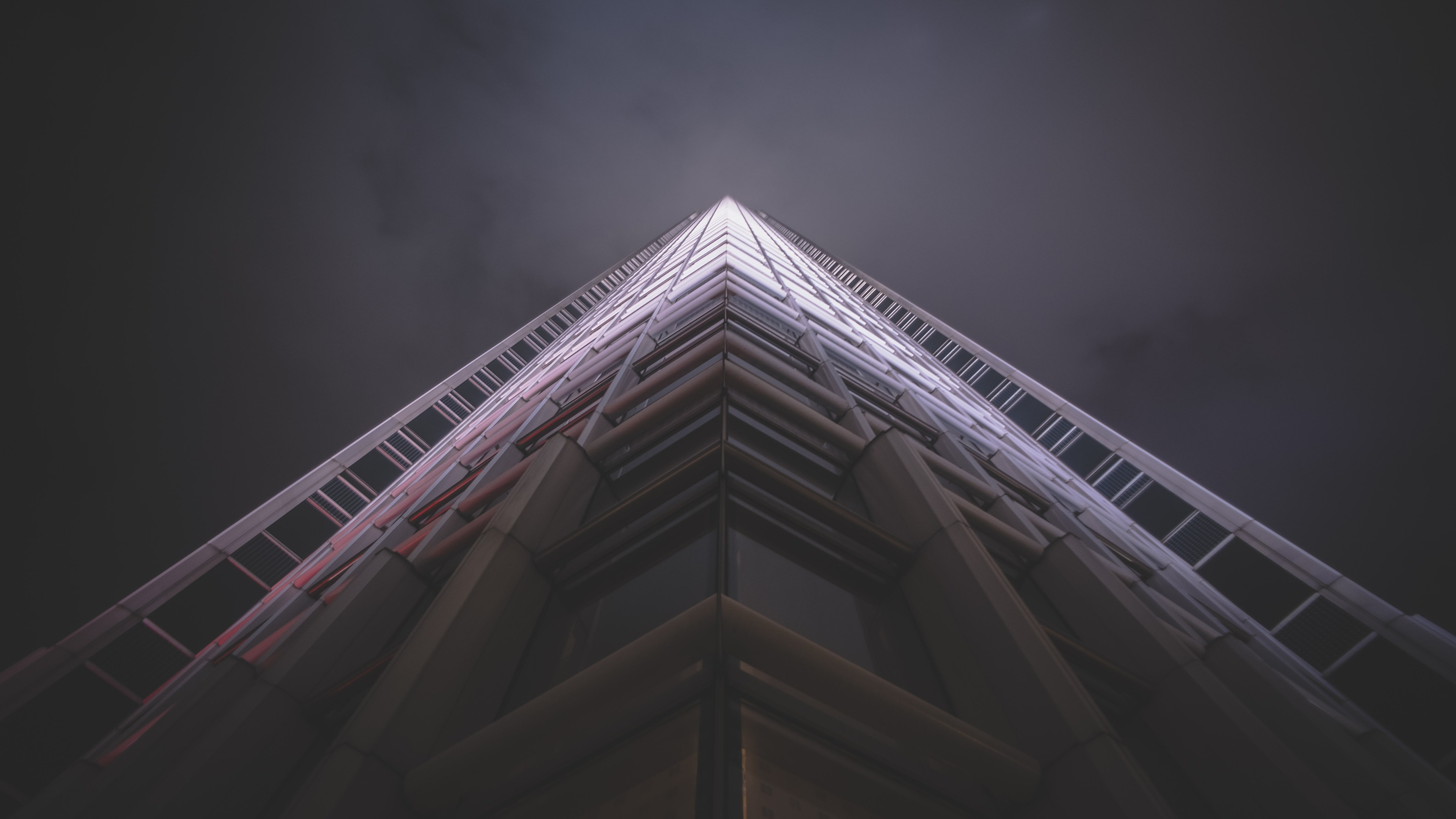 Very tall skyscraper building with shadow at base and pink and white light  at top