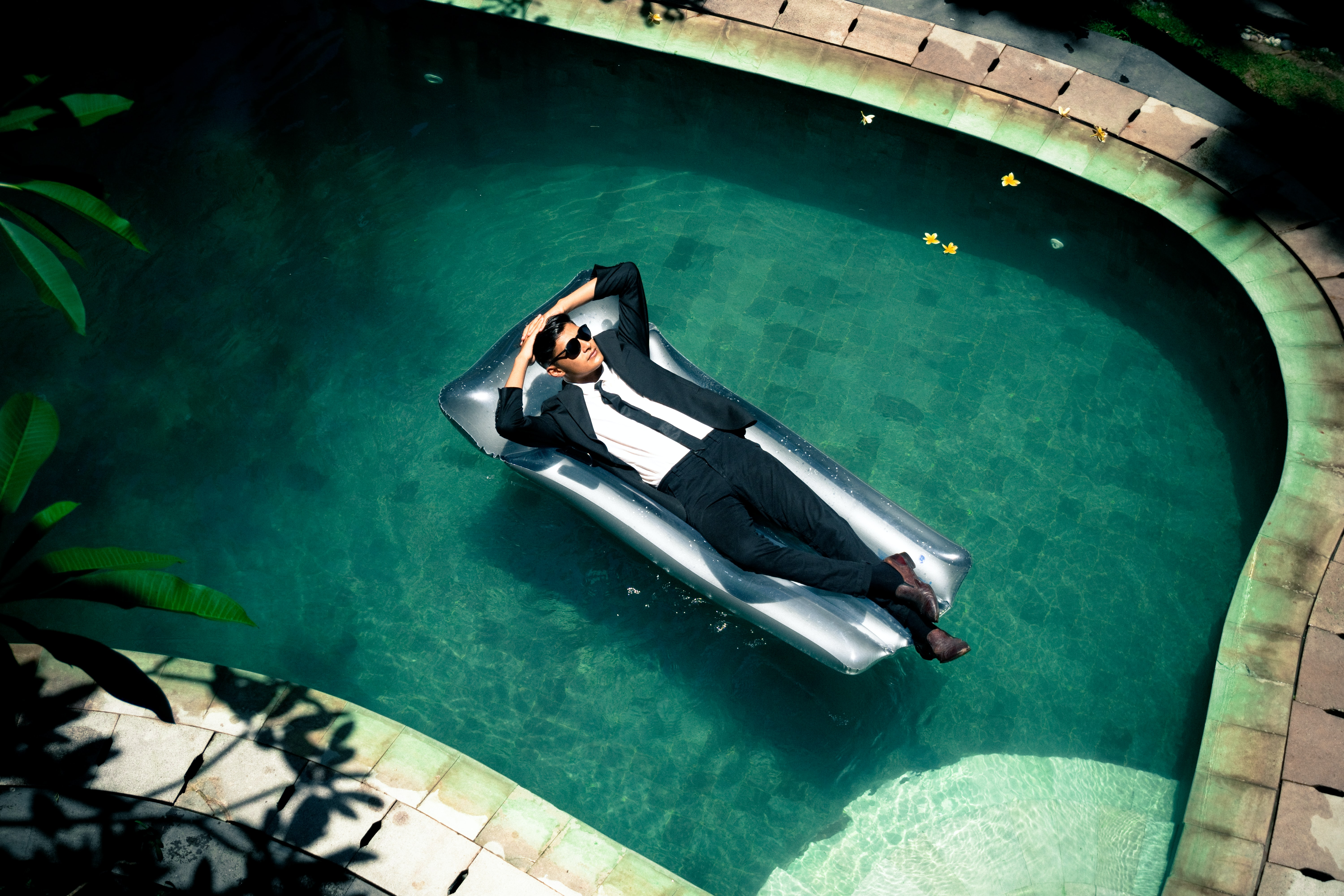 A man in a black formal suit on a float in a swimming pool