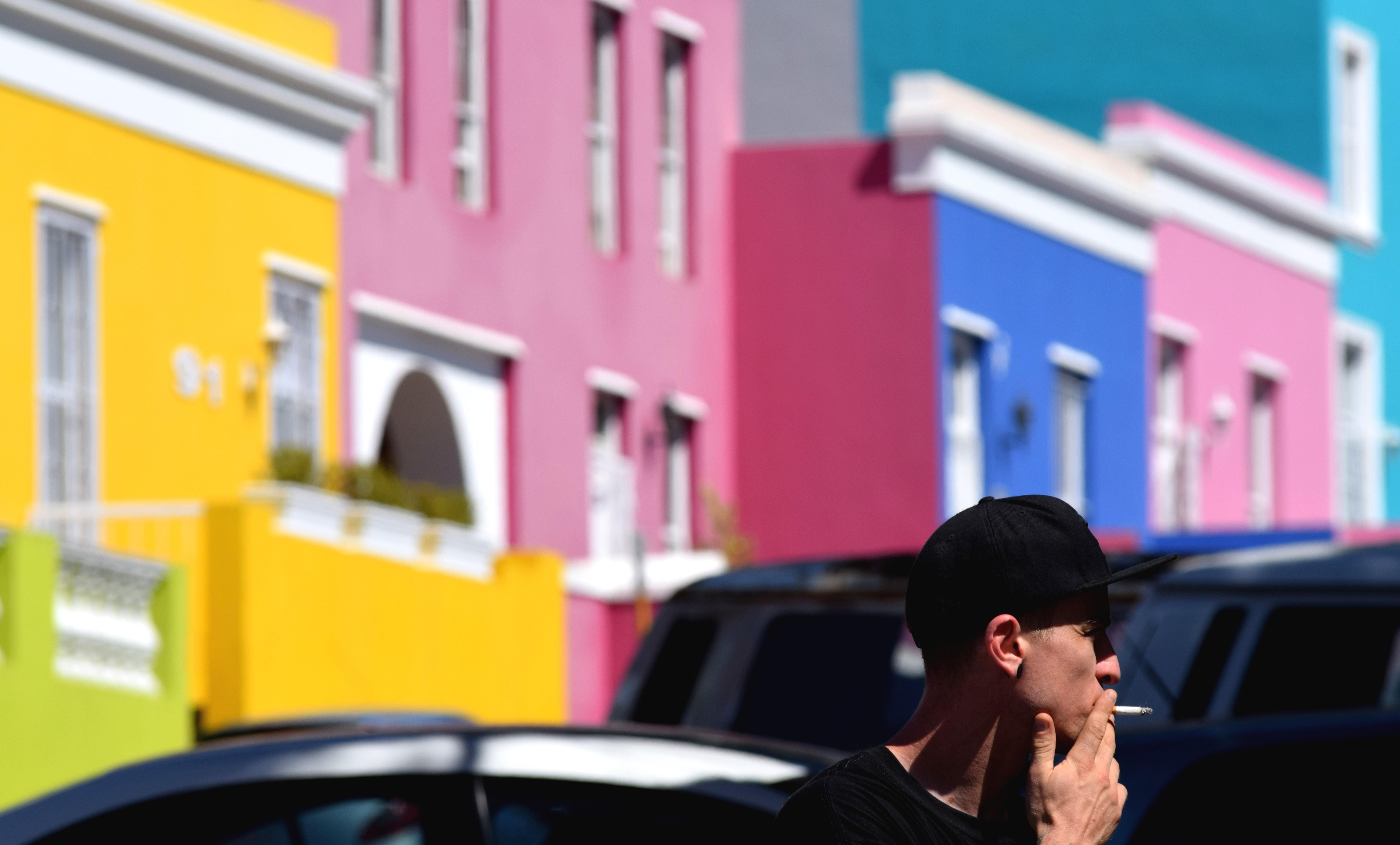man wearing black cap smoking