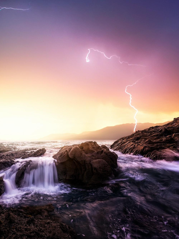 rock formation near sea under thunder light