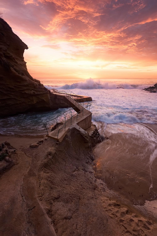 waves crashing on rocky coast during sunset