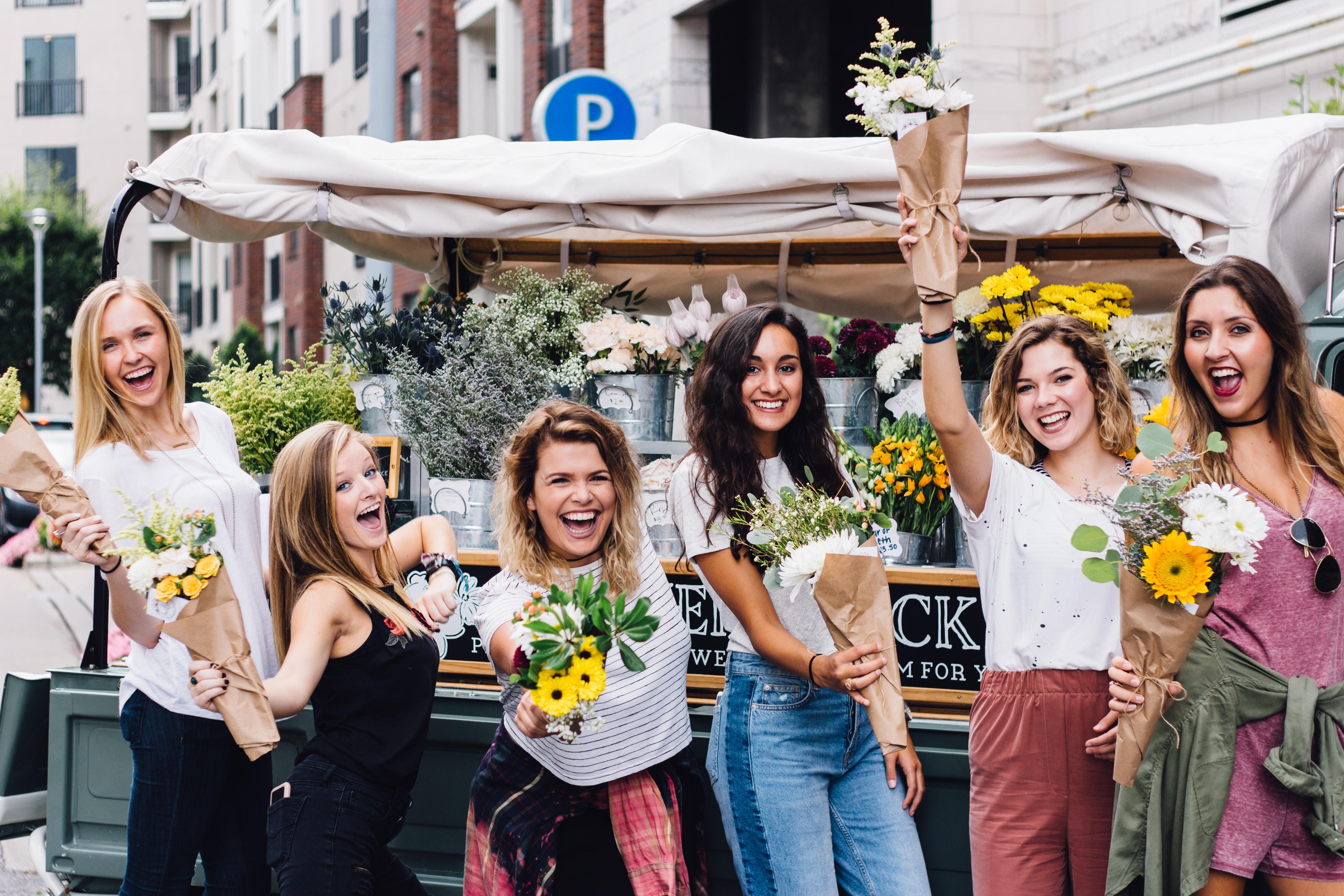 group of women holding flower bouquet beside flower vendor