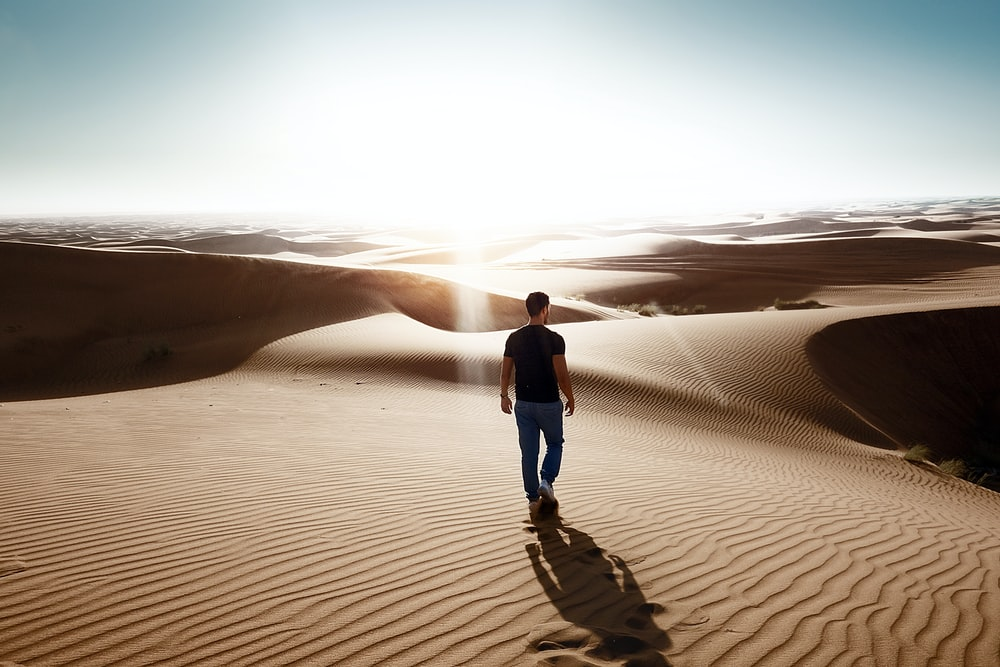 man walking through desert area