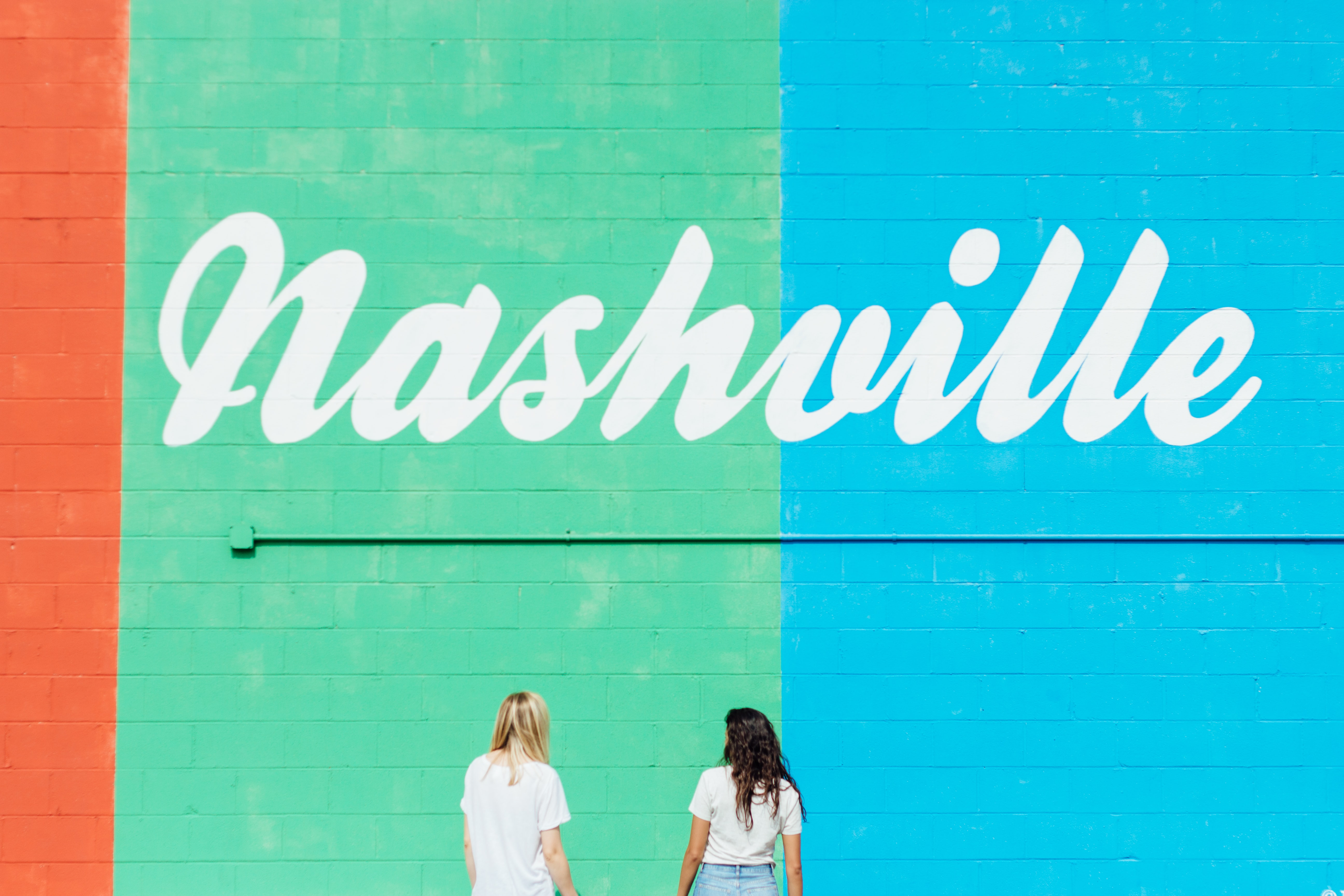 "Backs of two people in white t-shirts looking at a brightly-painted wall that says ""Nashville"""