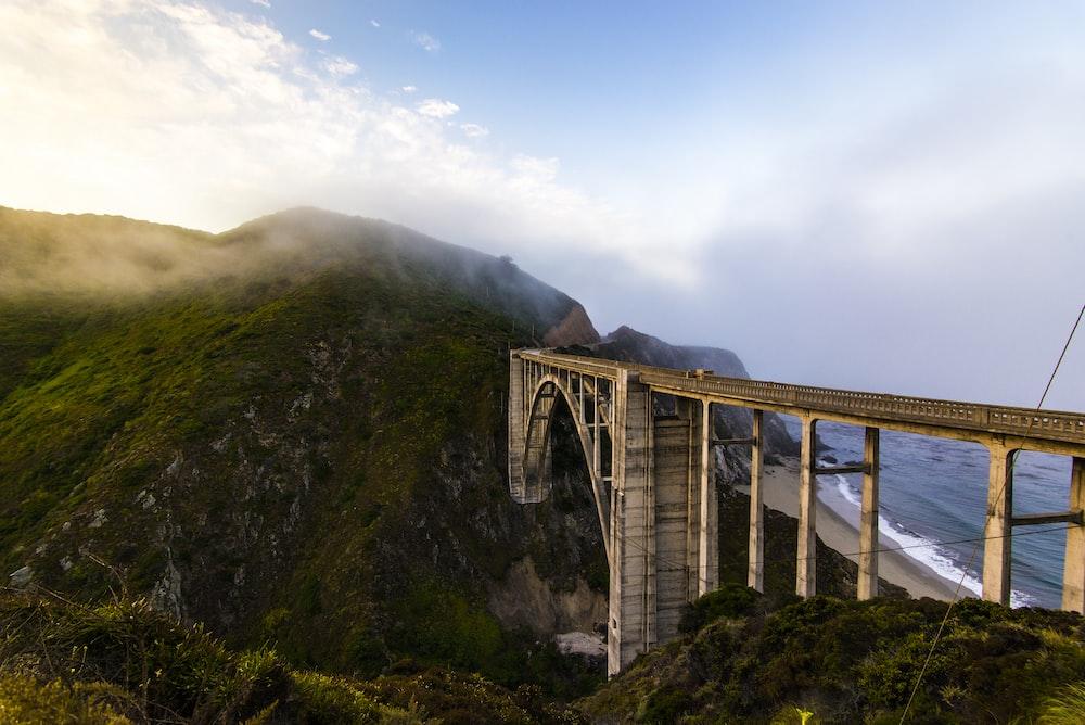 white bridge on green mountain during daytime
