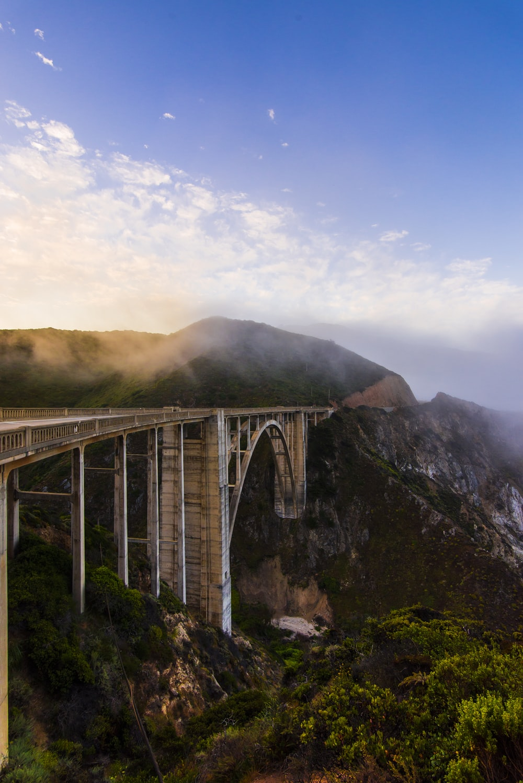 gray concrete bridge over green mountains during daytime