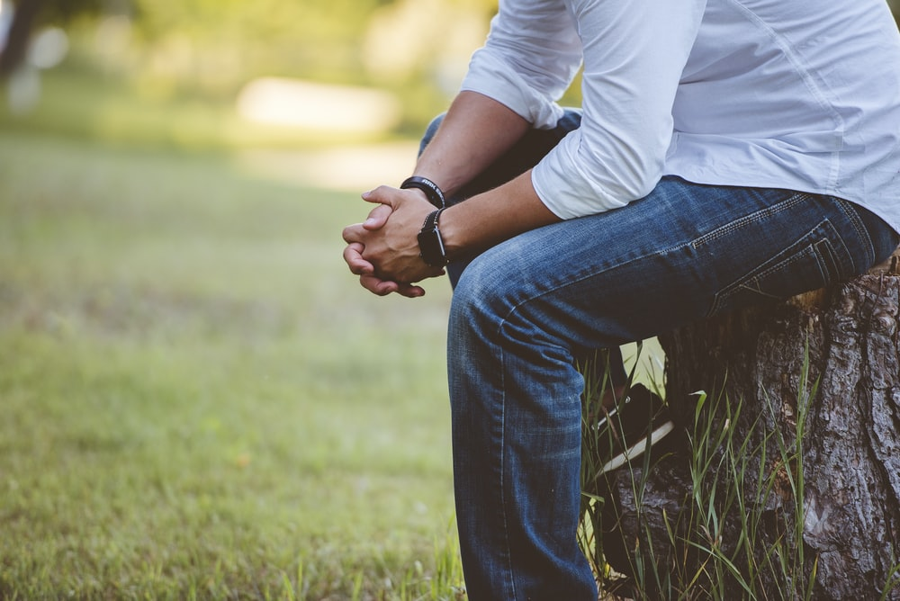 man wearing long sleeved shirt sitting