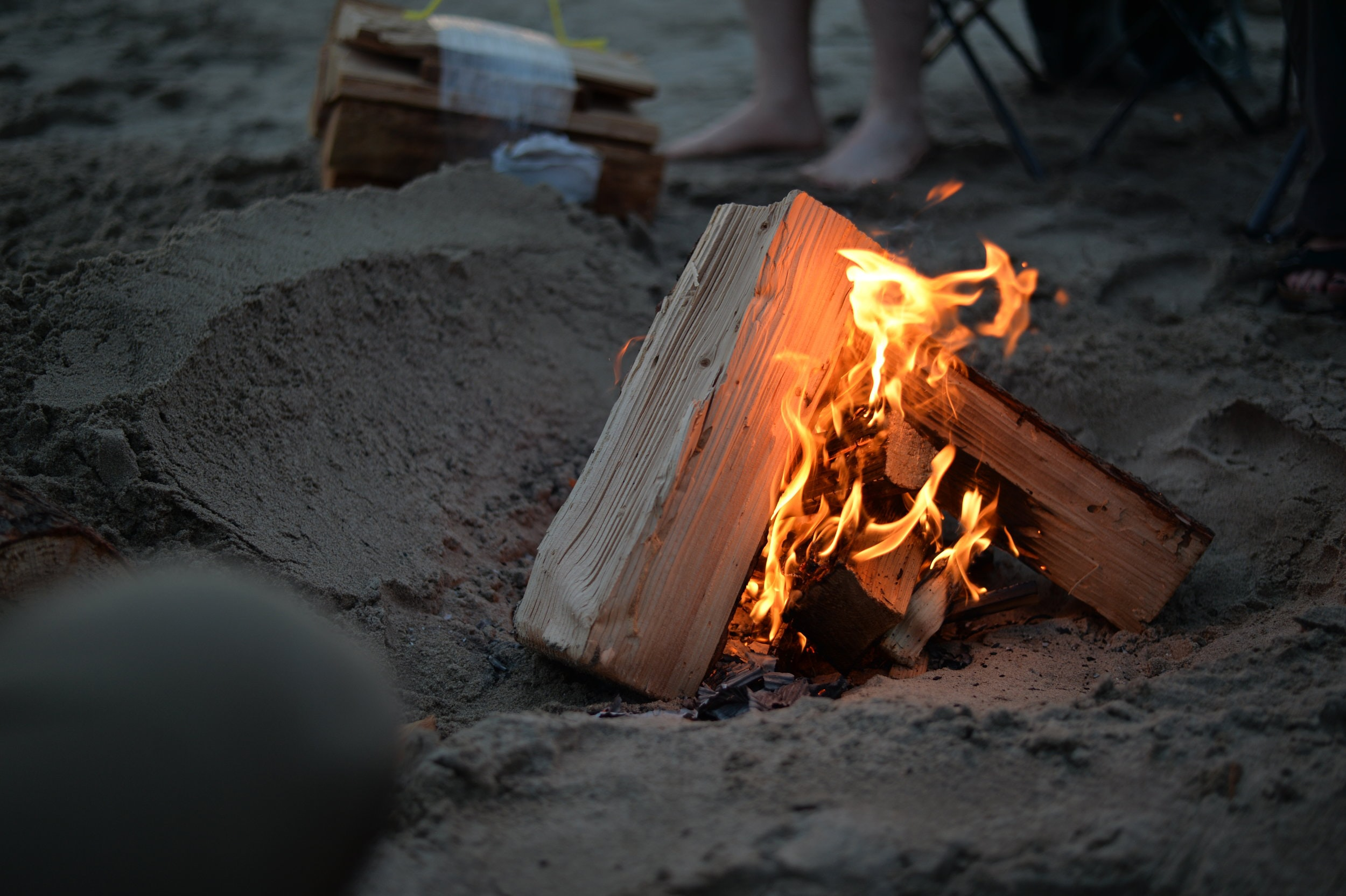 campfire on sand near person