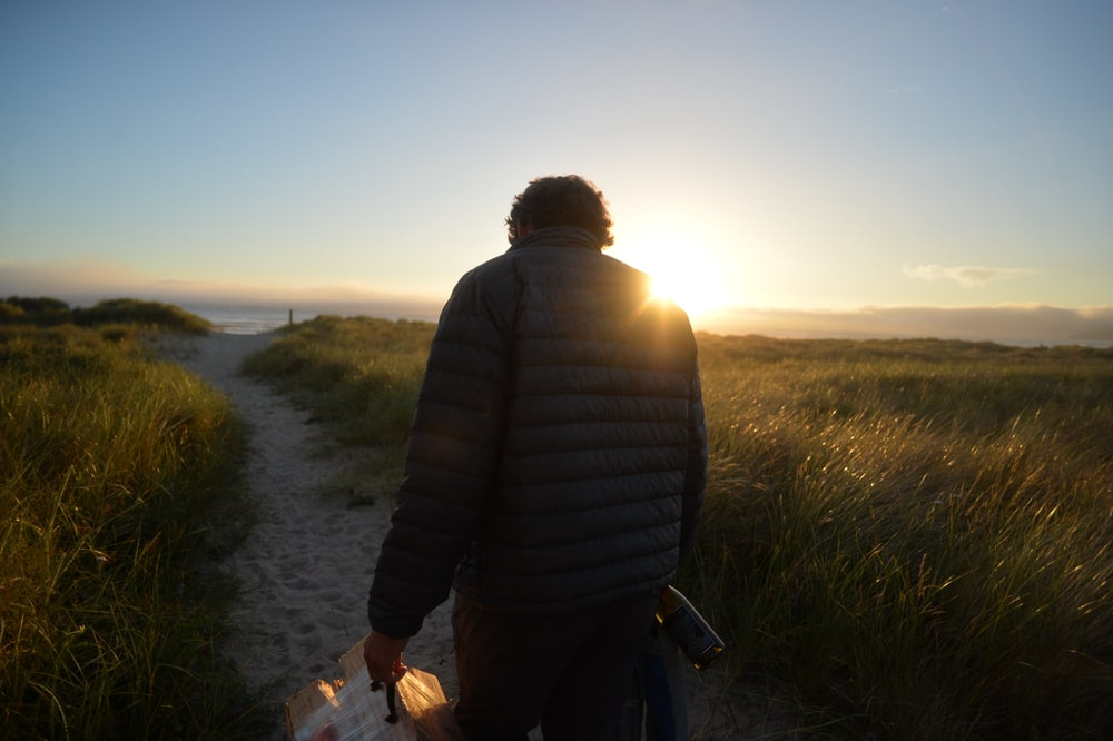 man walking across the road during sunrise