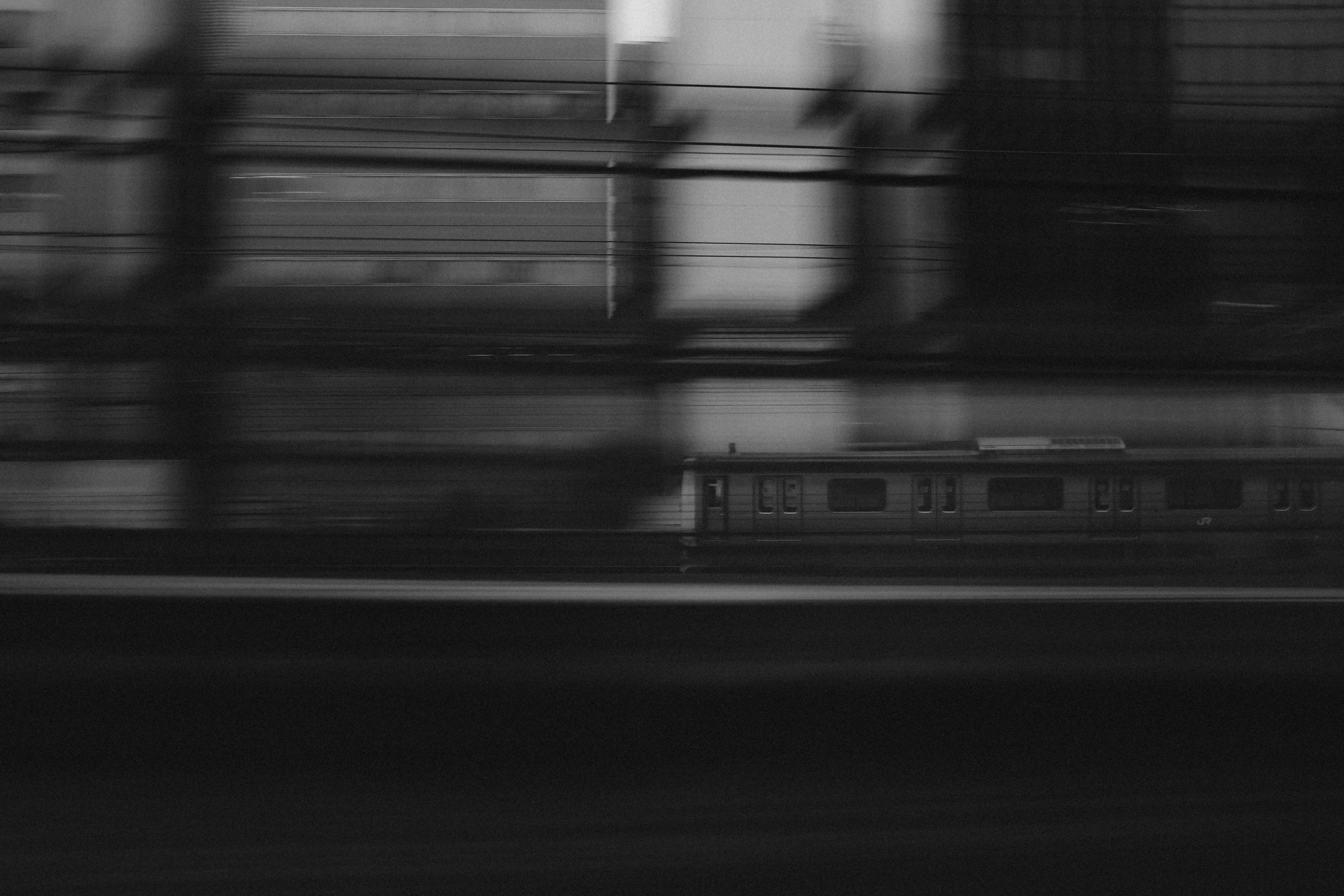 Black and white train moving past in a blur in Tokyo