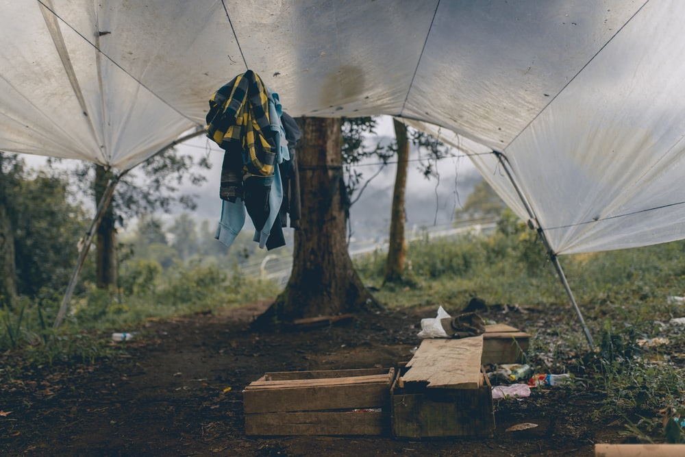A tent filled with clothing, wood, and empty plastic bottles