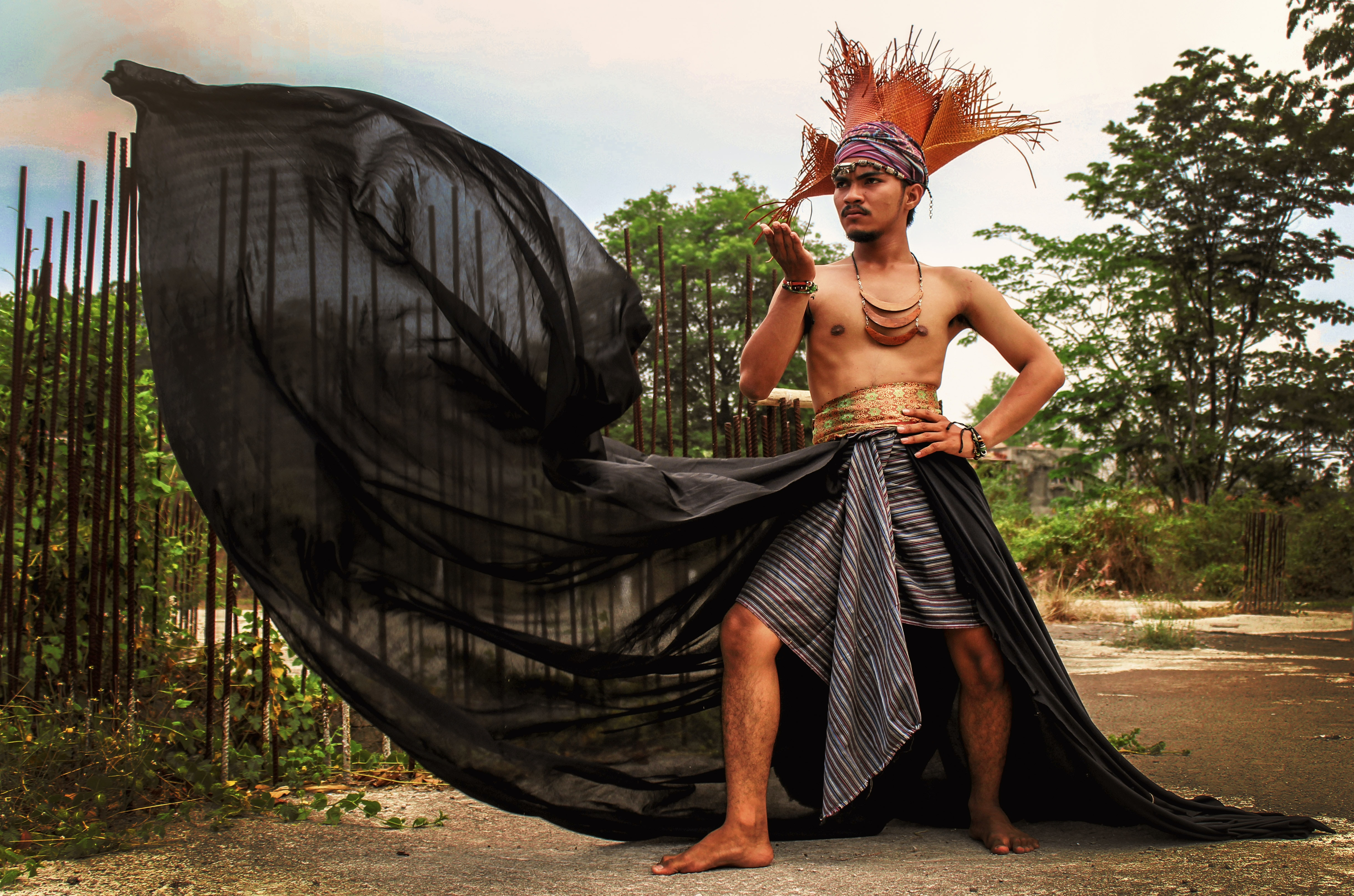 A dancer wearing a headdress and billowing sarong poses outdoors
