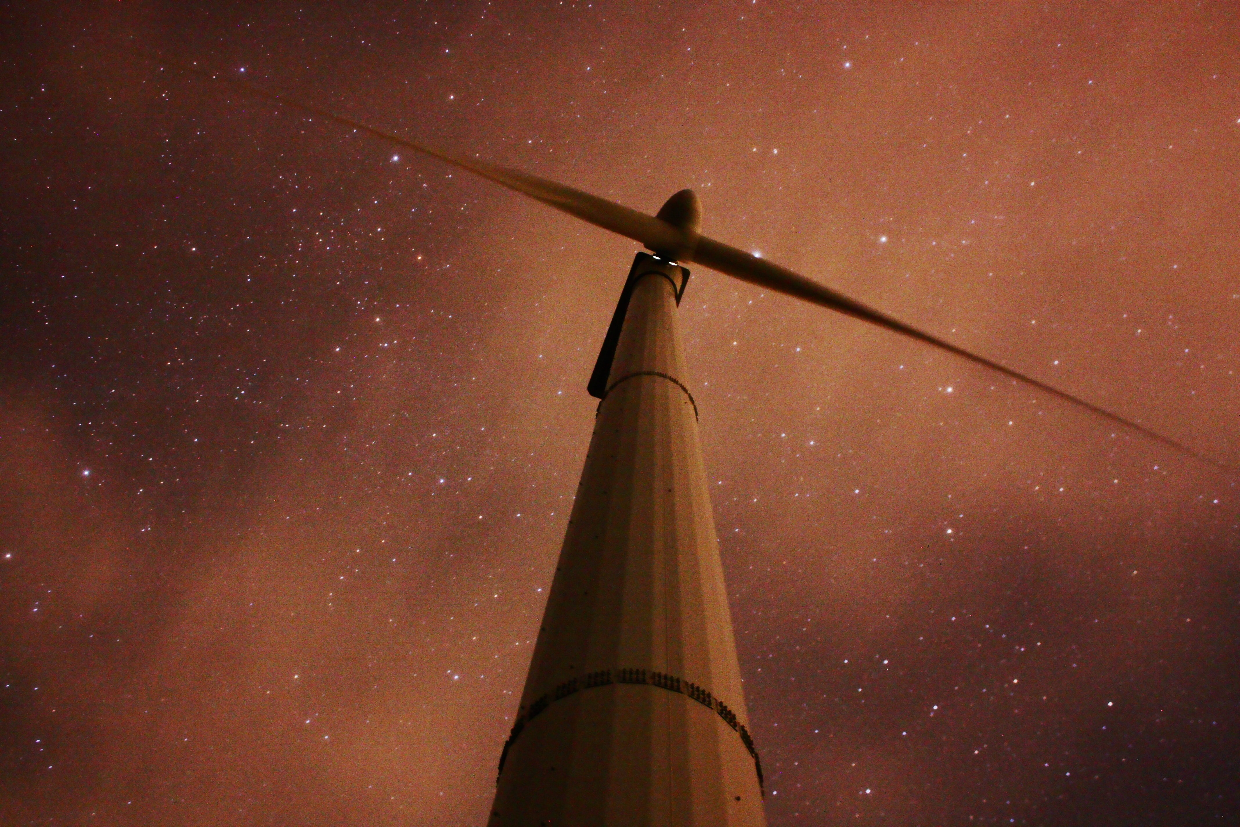 A low-angle shot of a wind turbine seen against a starry sky