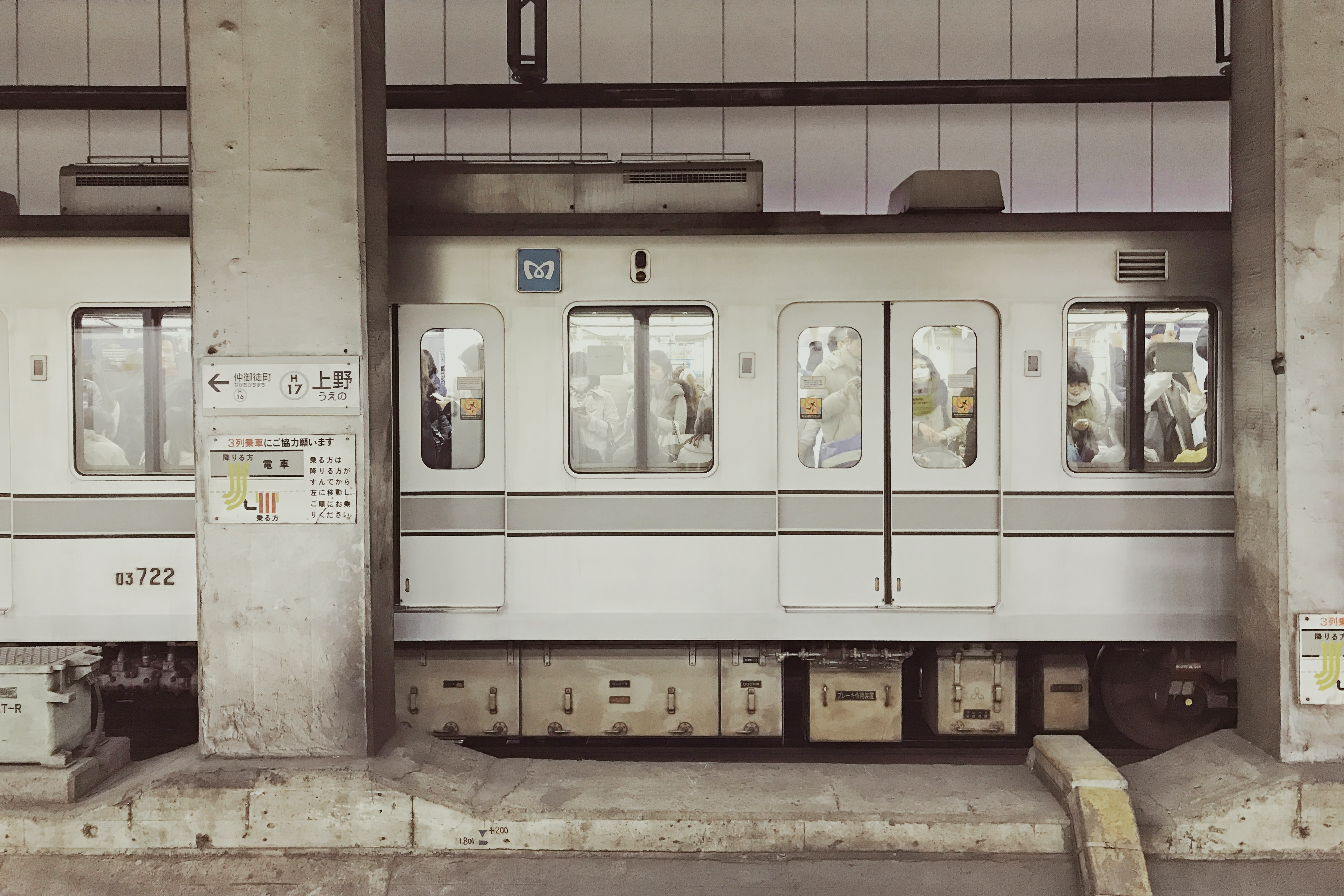 White subway car with doors and windows stopped at Ueno Station in between two concrete columns