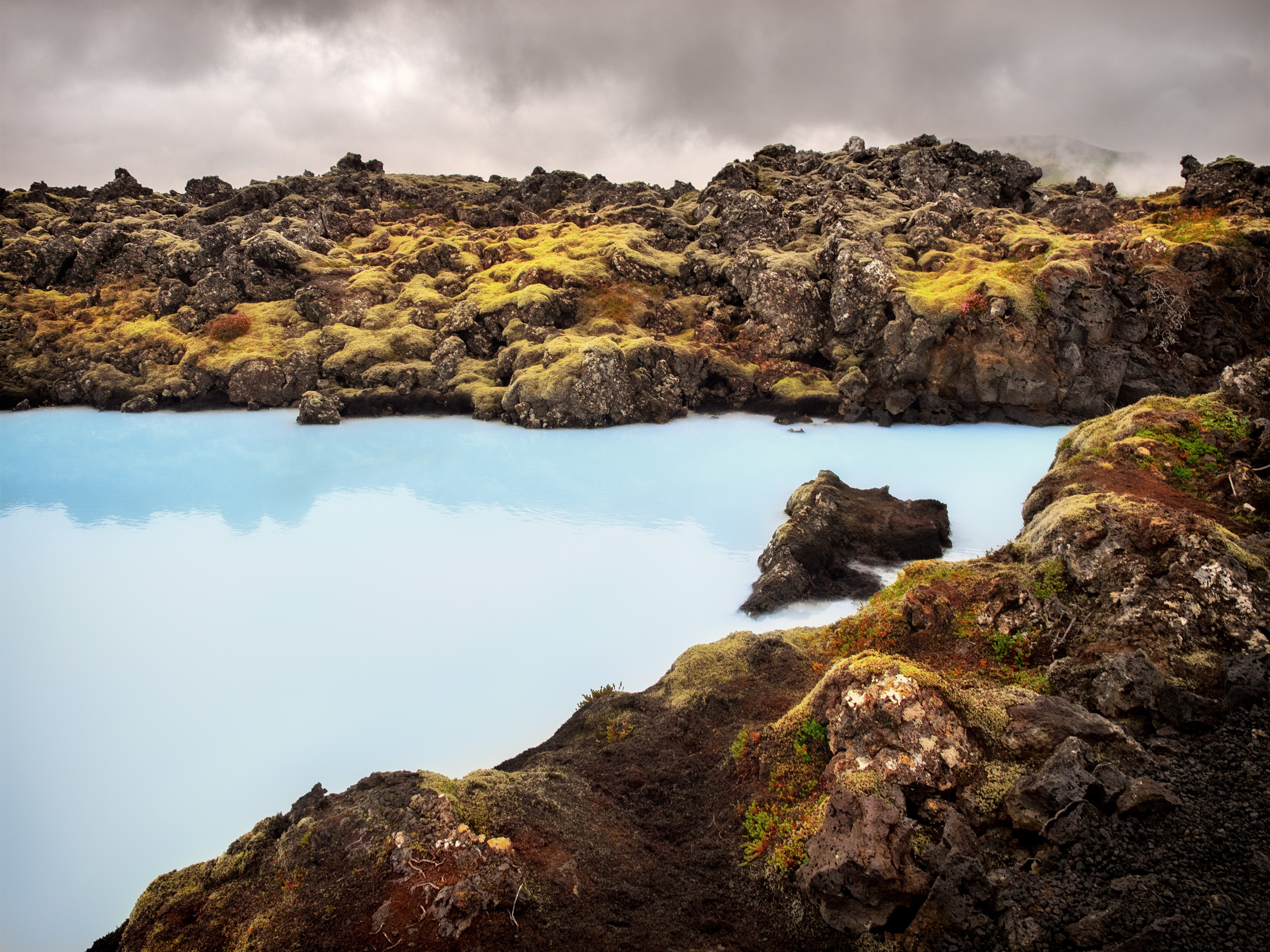 body of water between rocks under cloudy sky during daytime