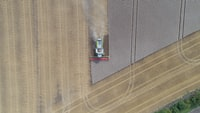A drone shot of a combine harvester in a field in Barton