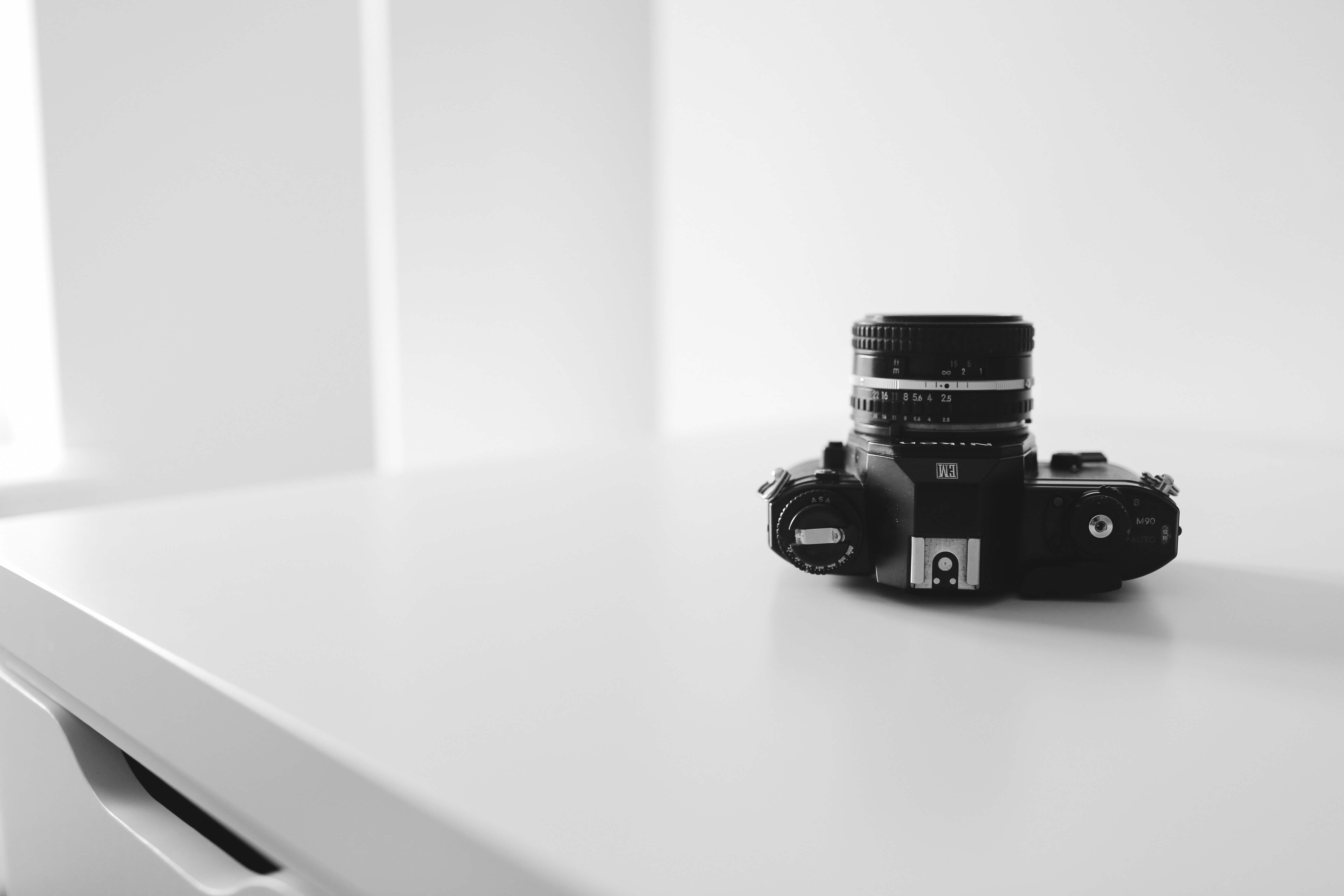 Monochrome of a camera sitting upside down on a table top