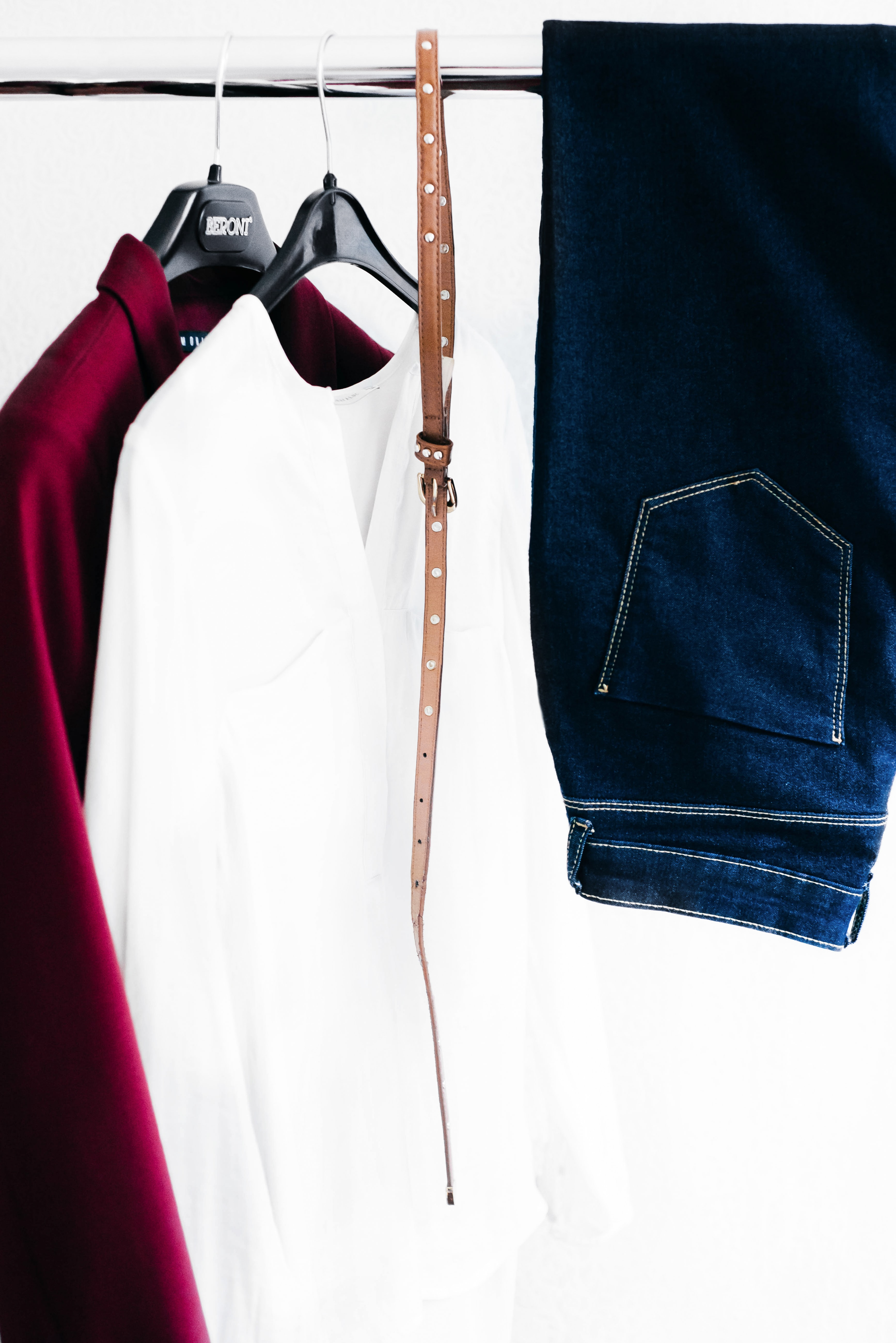 Shirts, a belt and a pair of jeans hanging in a wardrobe