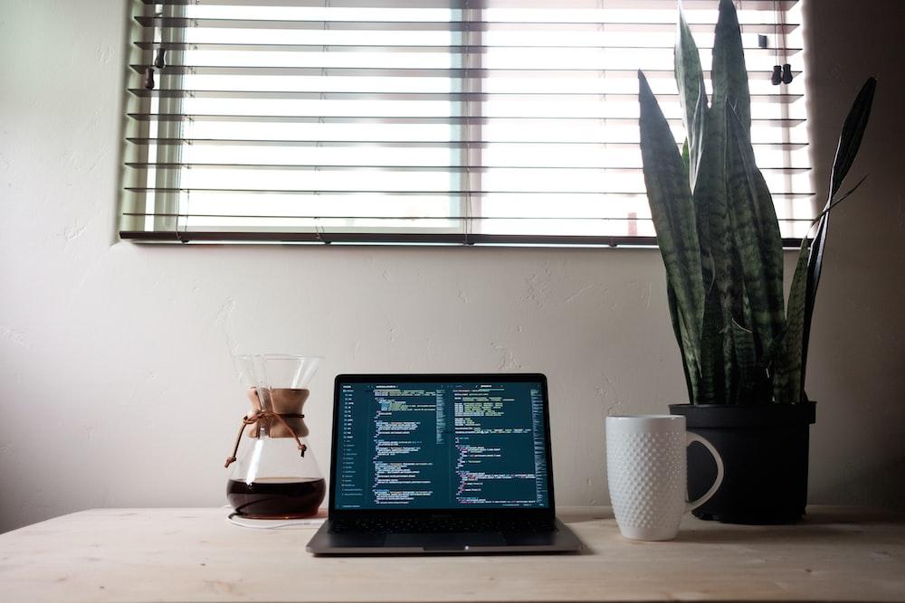black laptop computer beside white ceramic mug